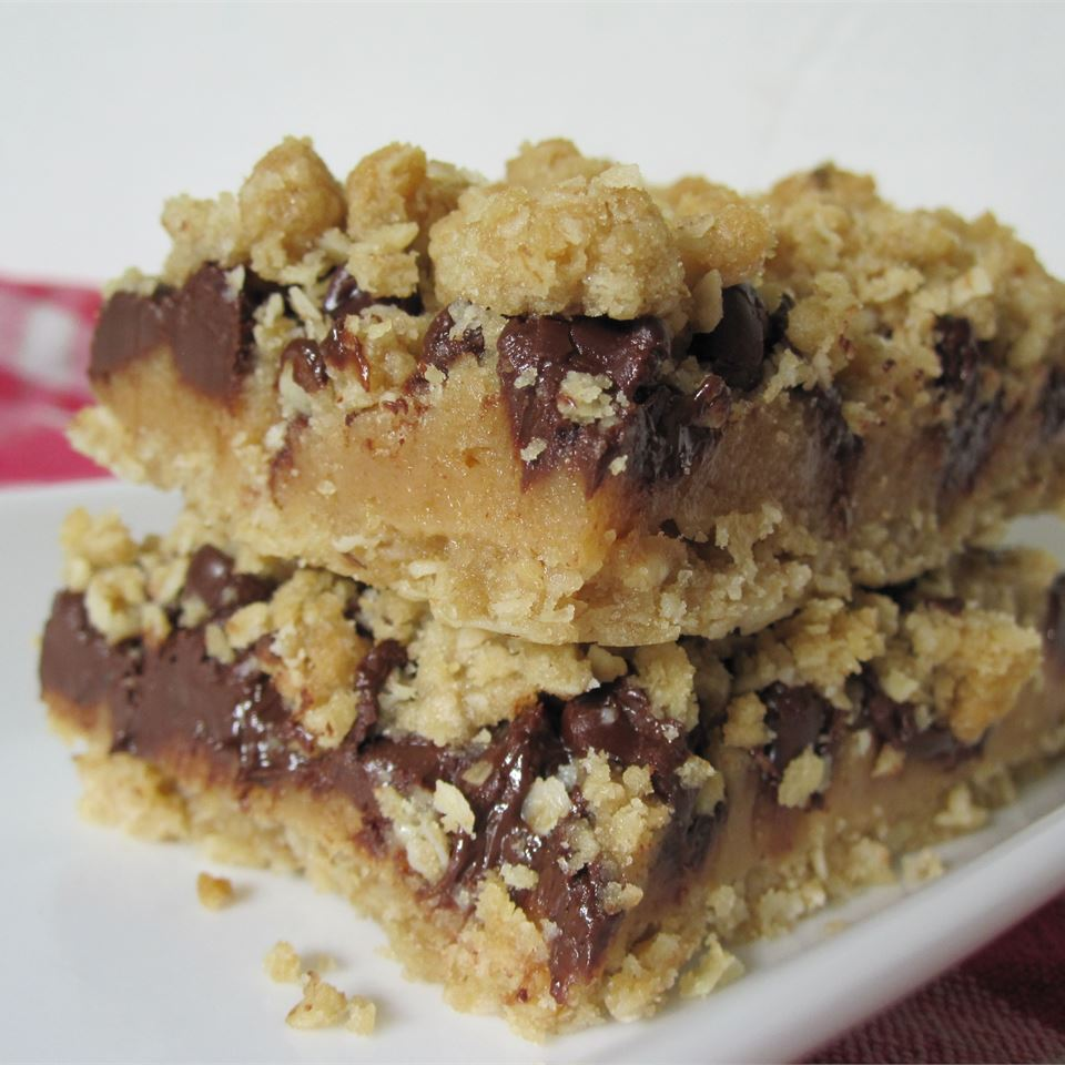 two stacked slices of oatmeal, chocolate, and caramel cookie bars