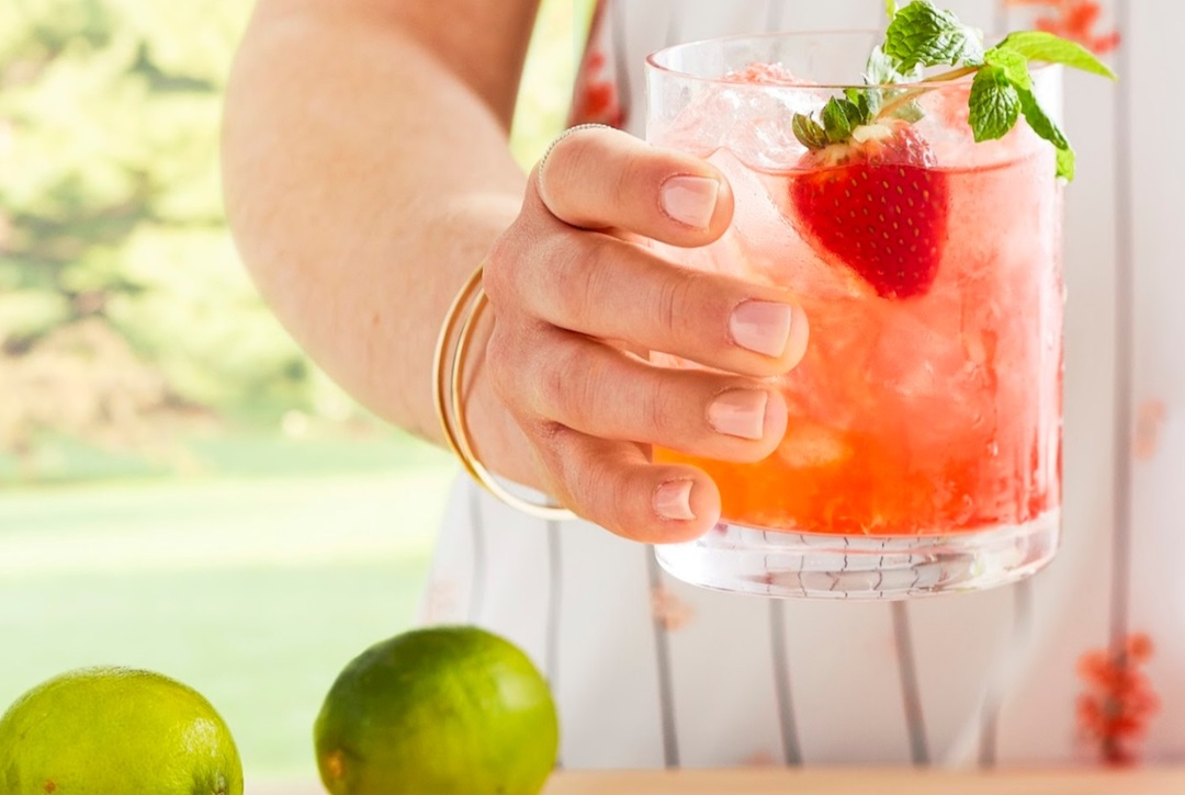 hand holding a strawberry lime cocktail in a short glass with strawberries and limes on a cutting board
