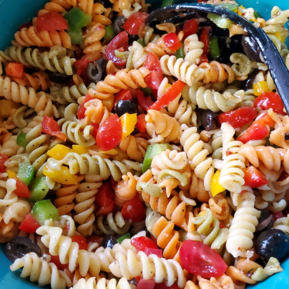 overhead shot of pasta salad with fusilli pasta, cherry tomatoes, olives, and diced peppers