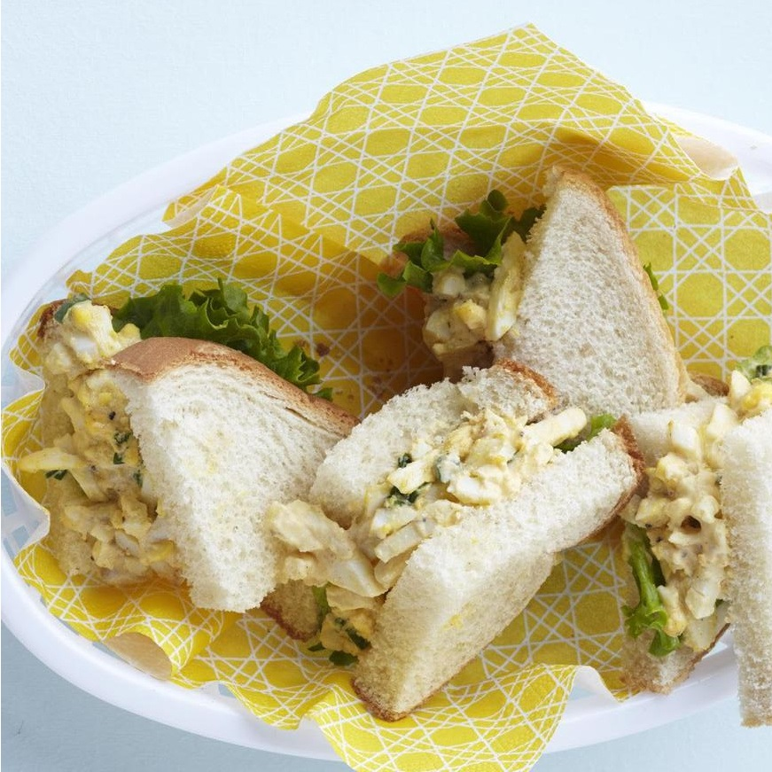 egg salad sandwiches sliced in triangles an on a plate