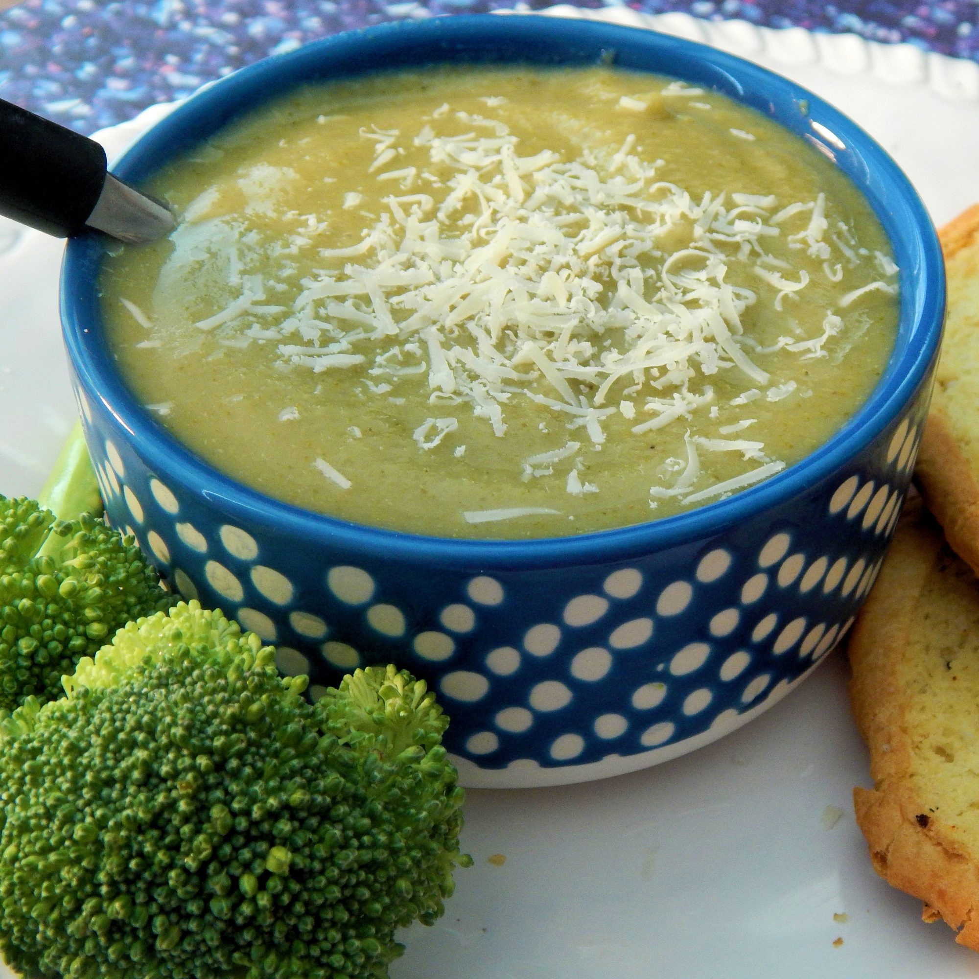 a blue bowl with broccoli soup and broccoli on the side