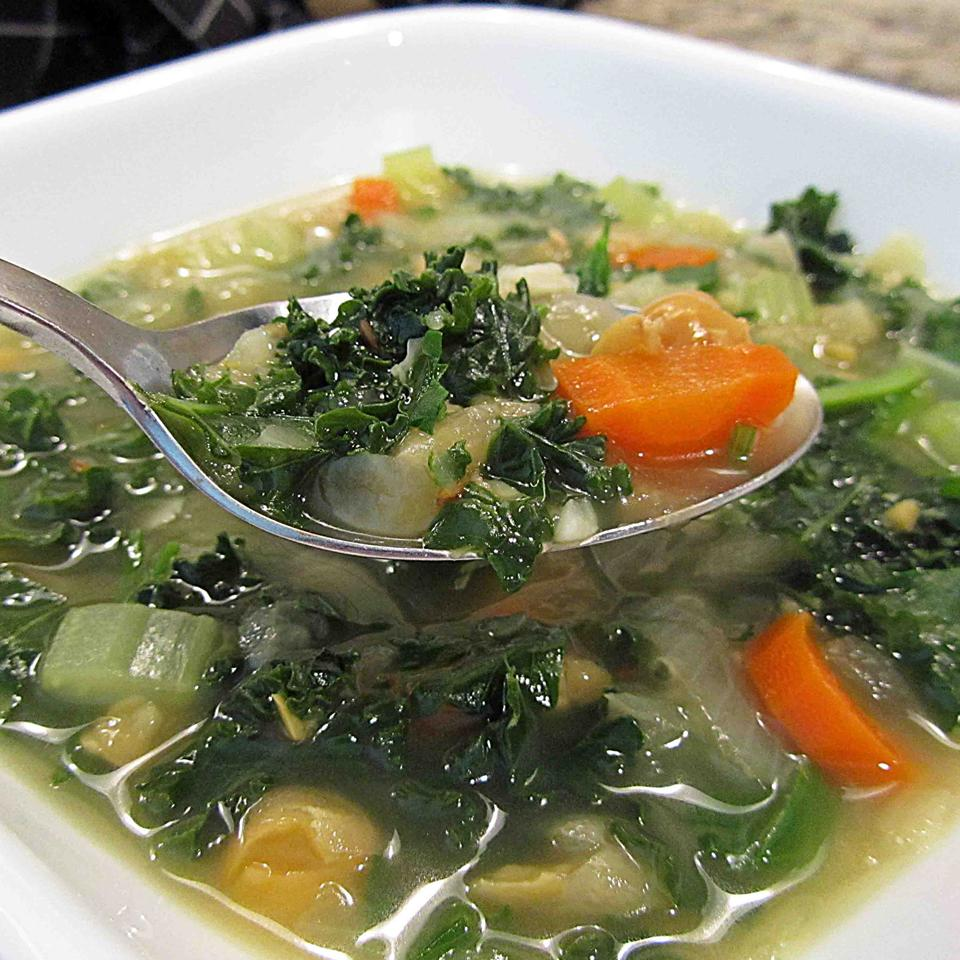 chickpea kale soup in a white bowl with a spoon