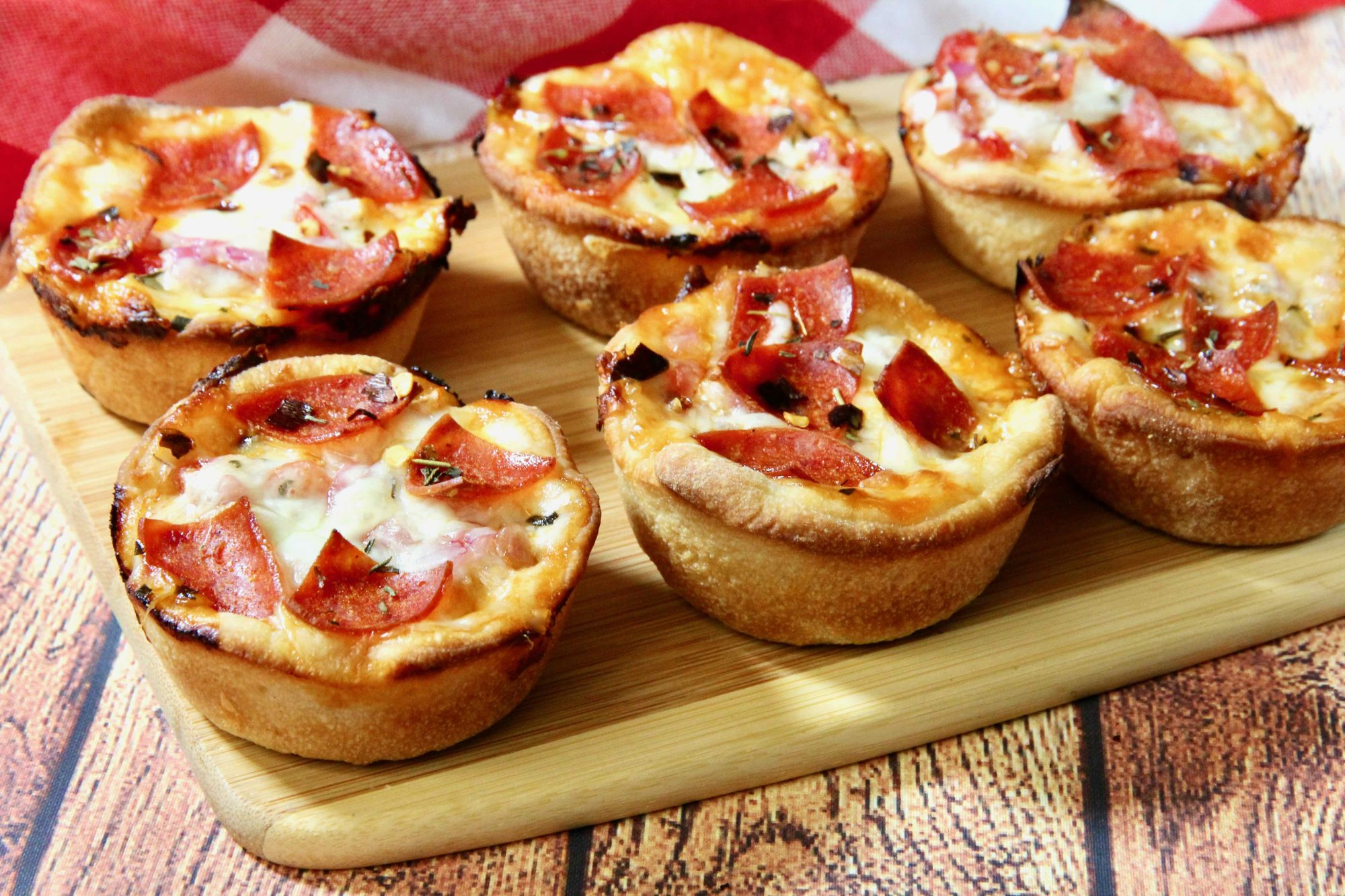 six pizza cupcakes on a wooden board