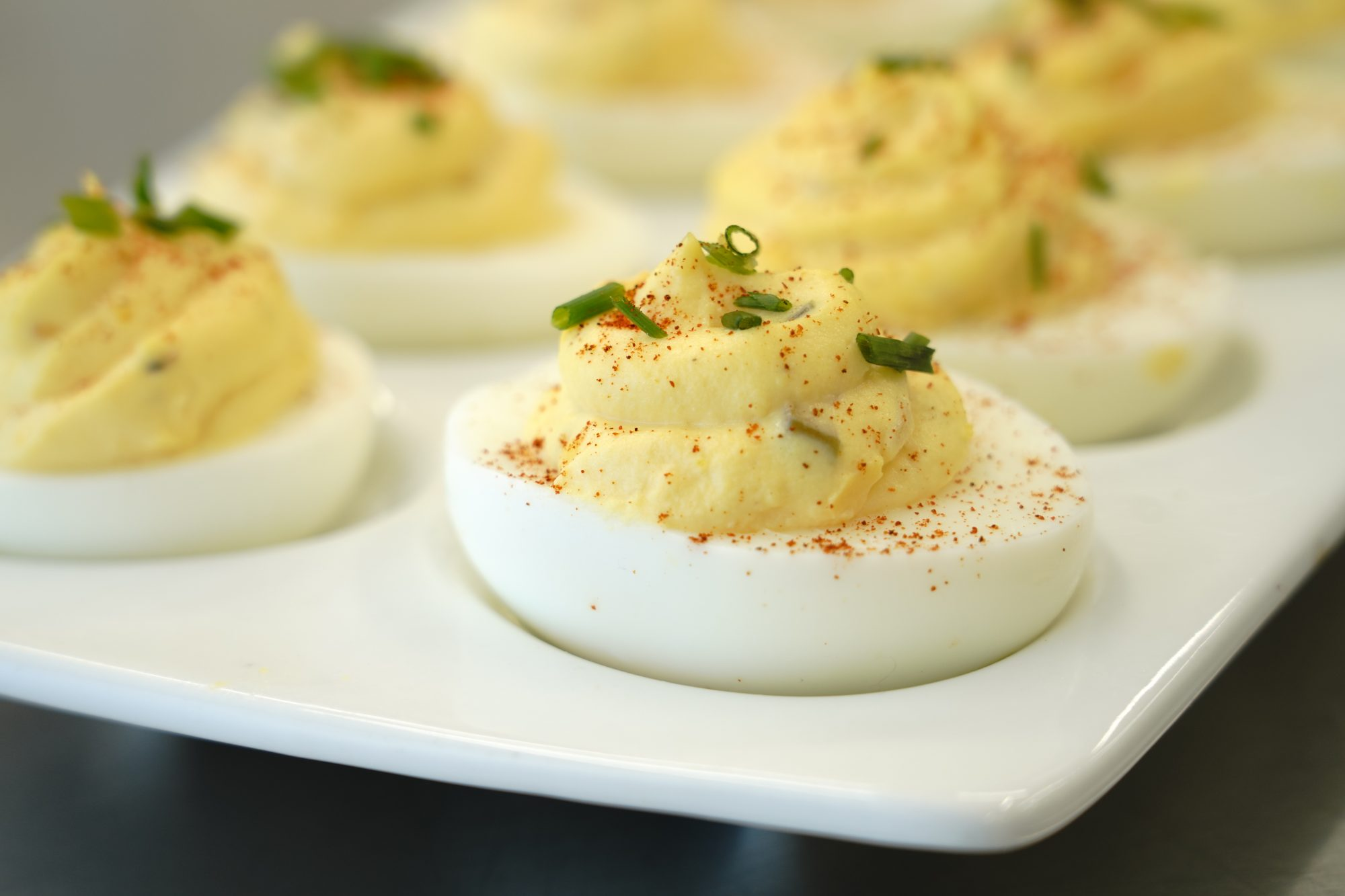 deviled eggs topped with paprika and minced chives on a deviled egg tray