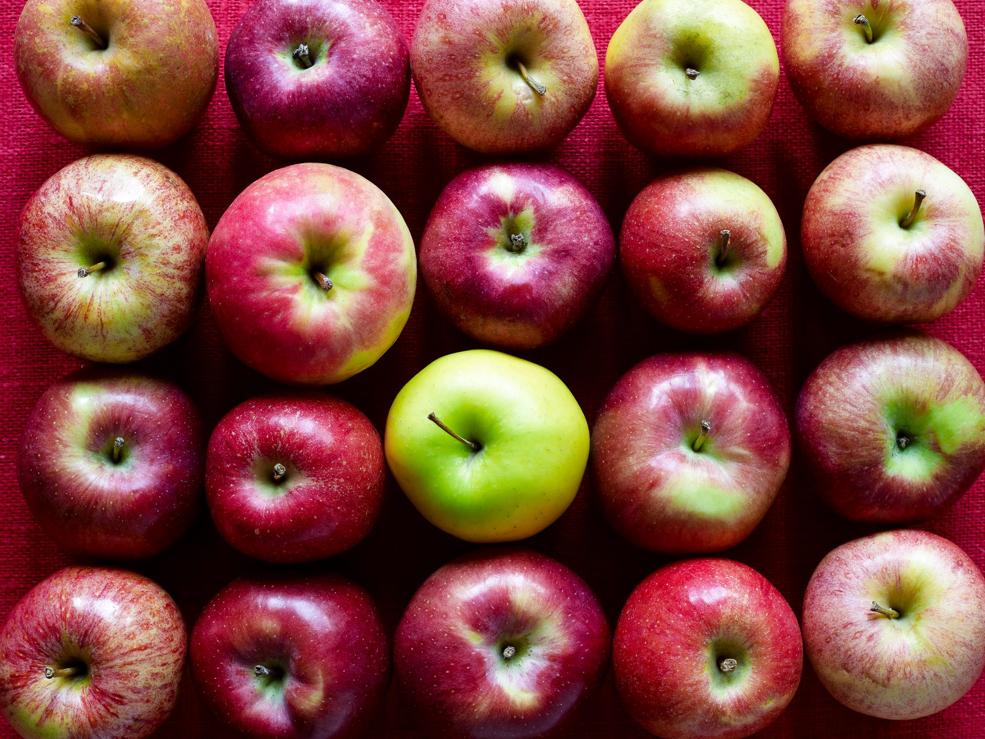 multiple red apples and one green apple