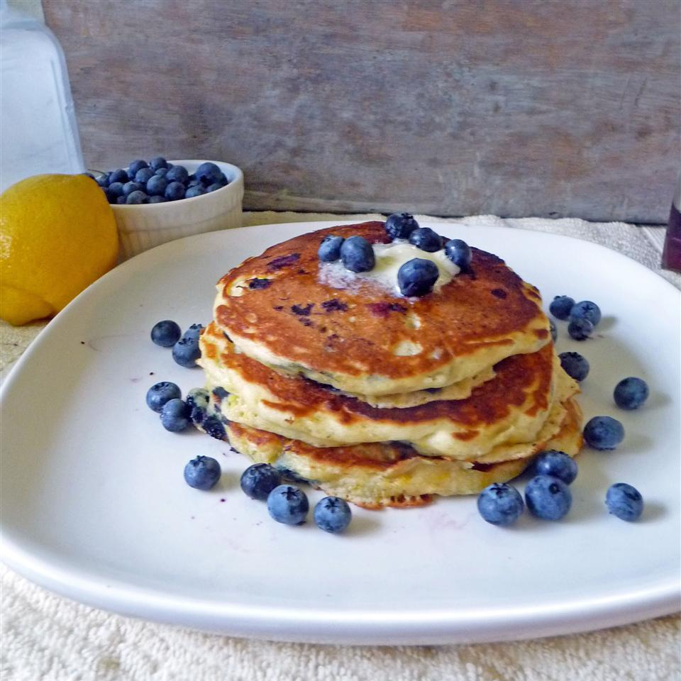 a stack of pancakes with fresh blueberries on top and scattered around the white plate