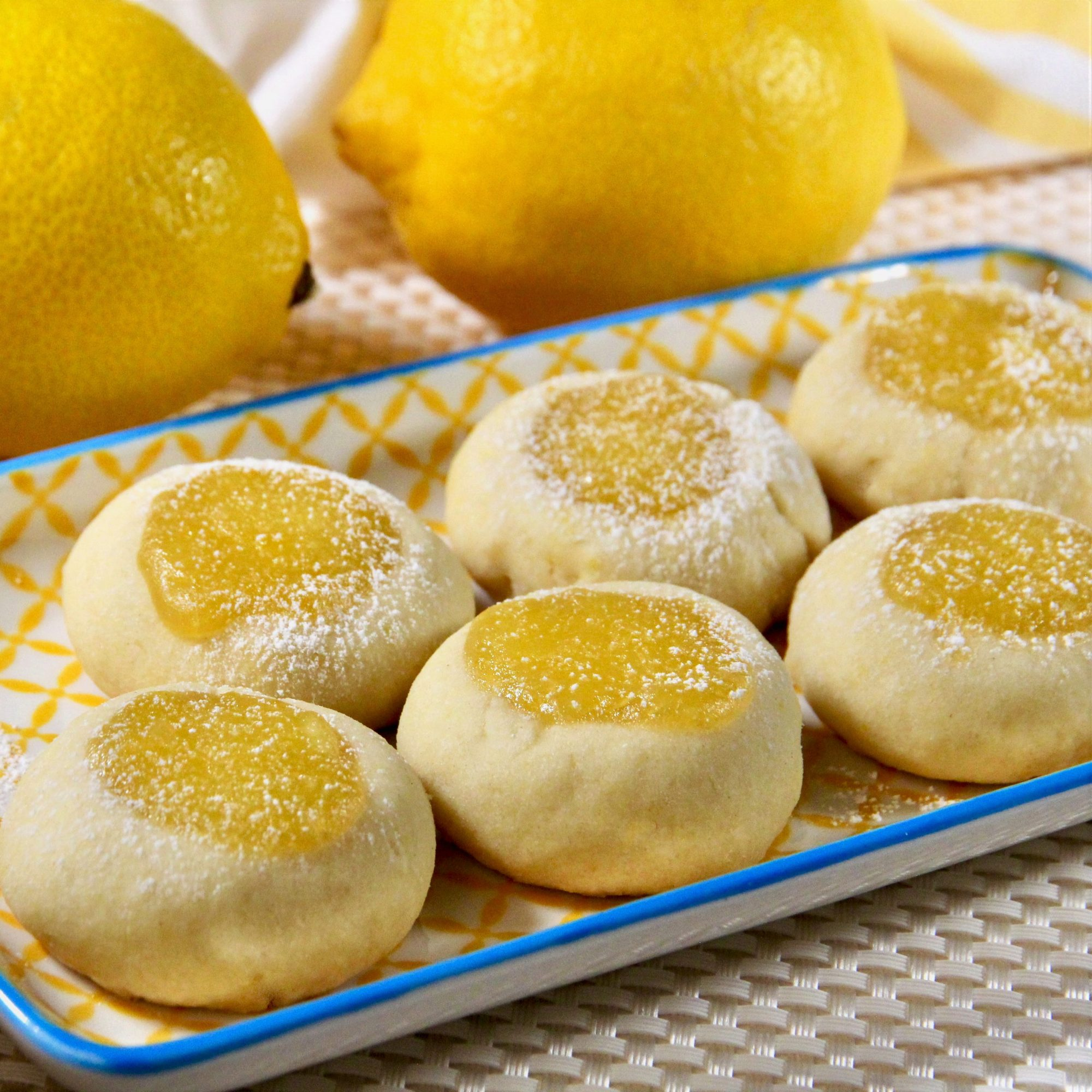 a tray of lemon curd thumbprint cookies with lemons in the background
