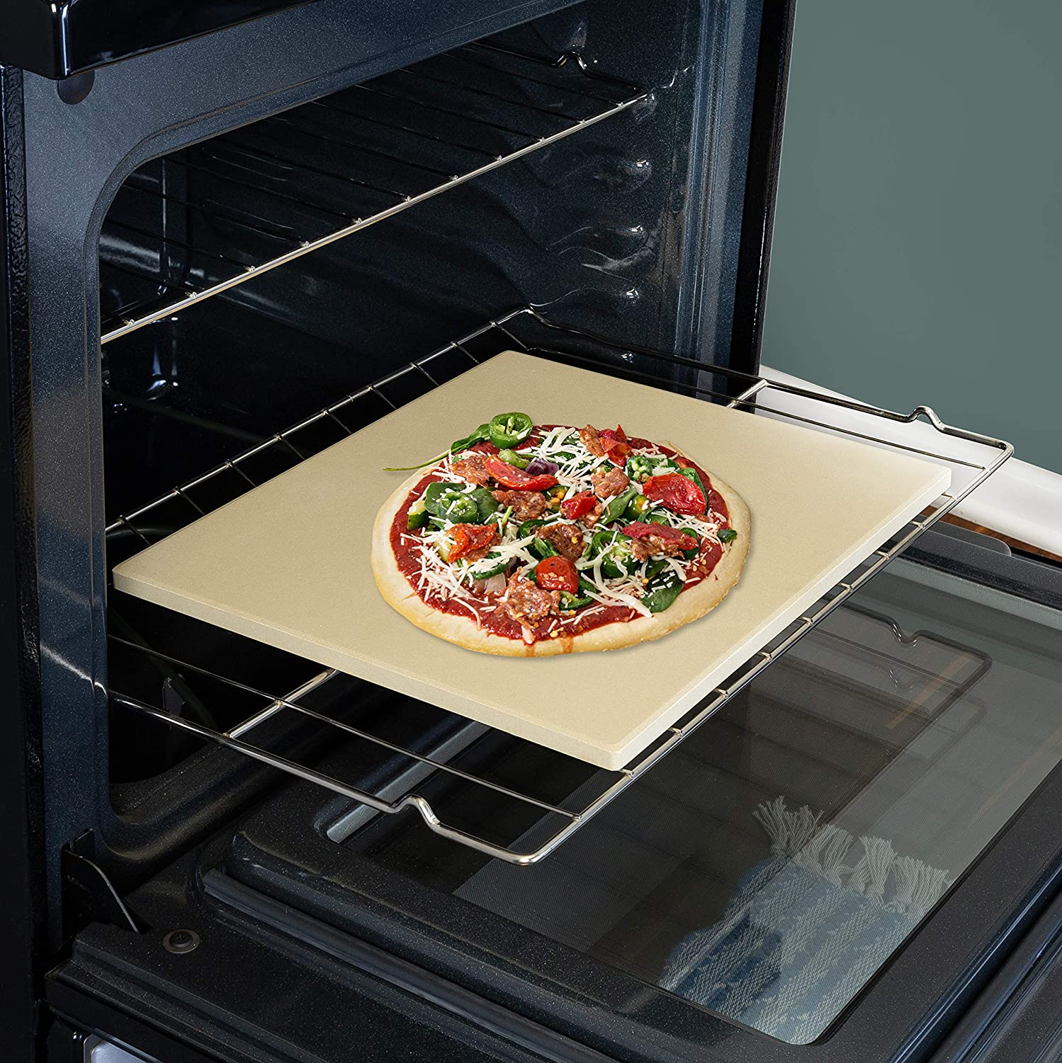 rectangular pizza stone with pizza on it on oven rack