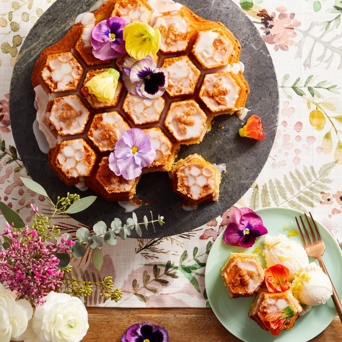 overhead view of apricot cake baked in honeycomb pattern cake pan and served with ice cream and edible flowers