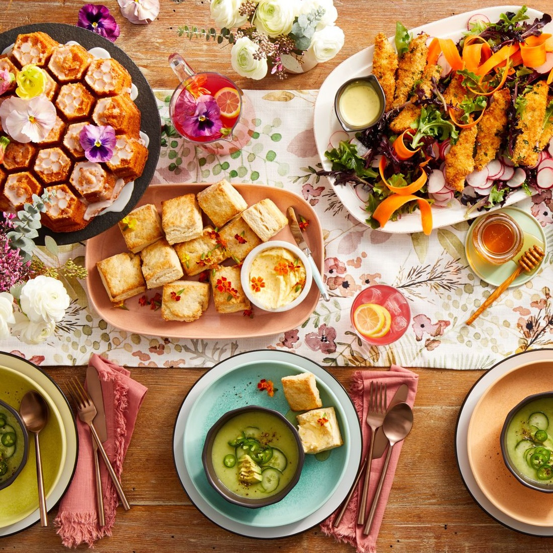overhead shot of brunch table set with cake, biscuits, green gazpacho, lemonade, and flowers