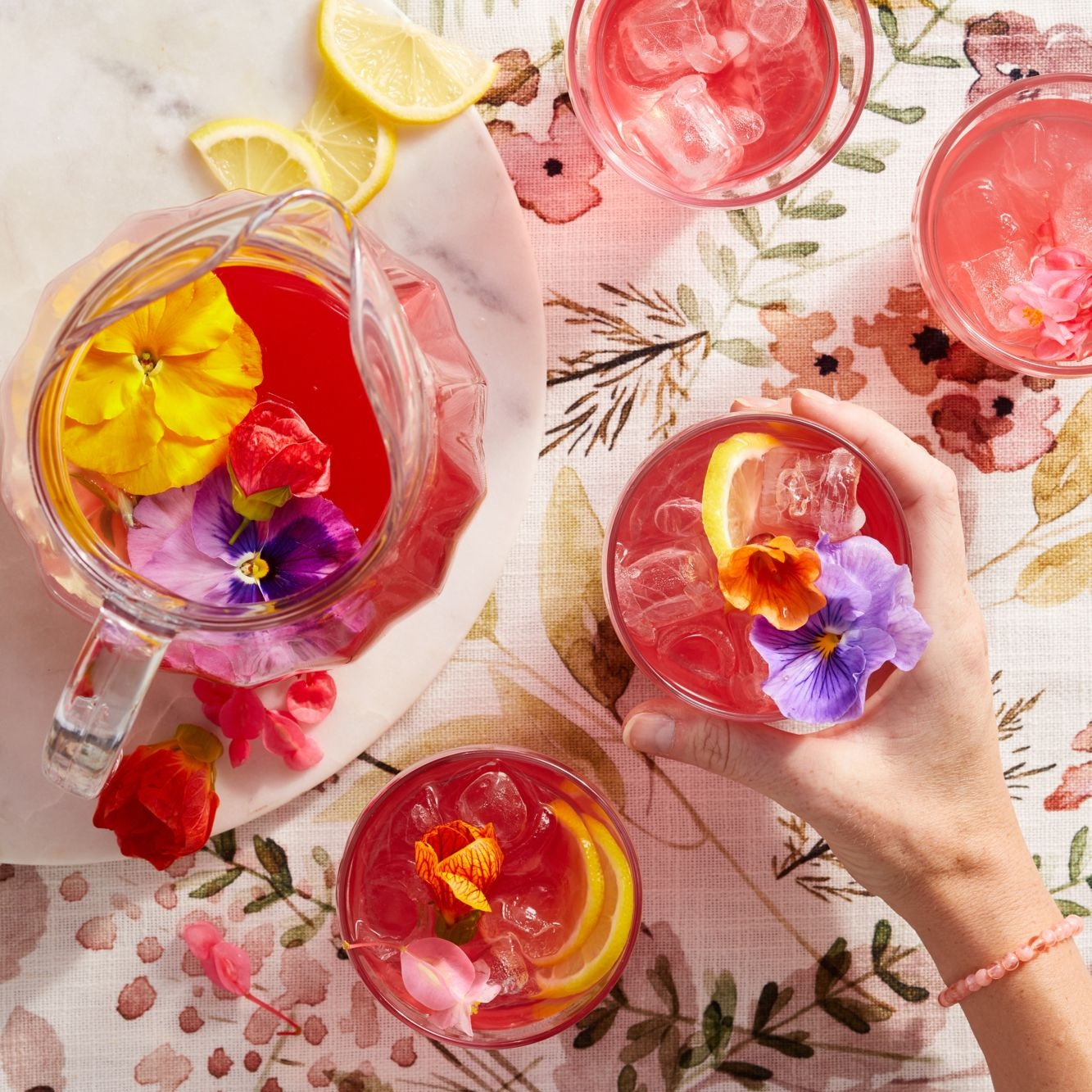 overhead shot of a pitcher and glasses of lavender lemonade with hibiscus garnished with citrus slices and edible flowers