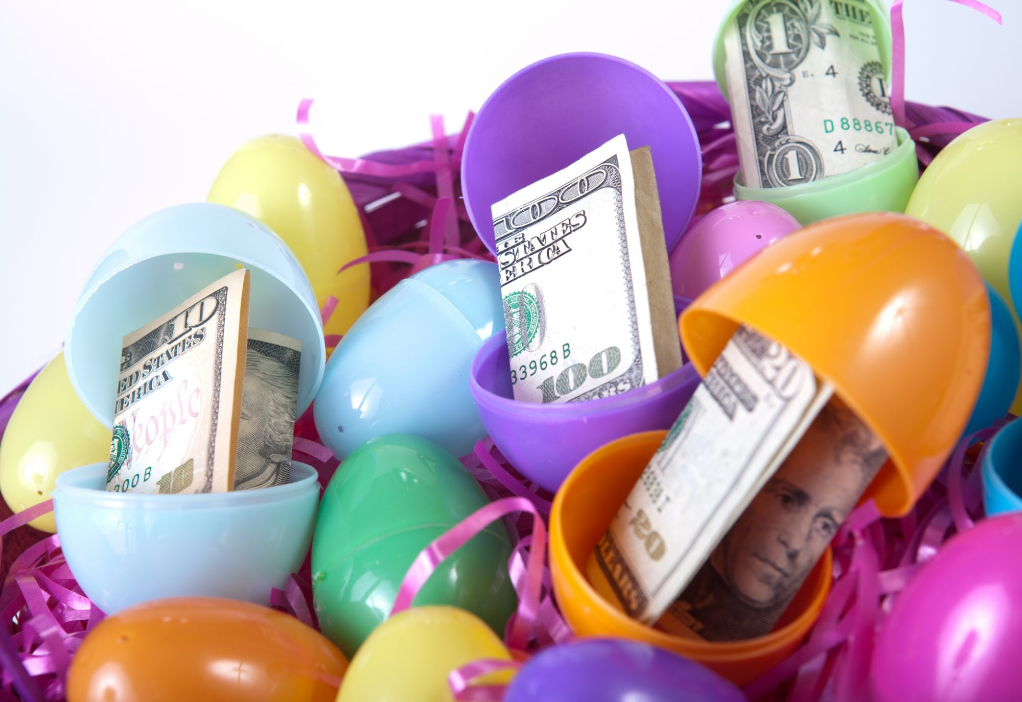 An Easter basket full of eggs with paper money on white background. Focus on the $100 bill in the center.