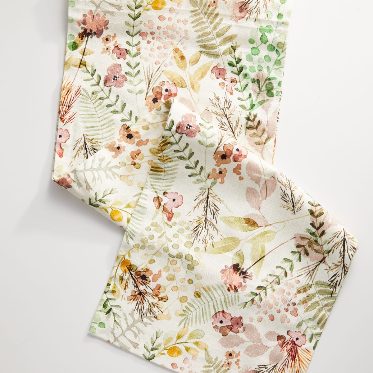 fabric table runner with a spring themed floral pattern of flowers and ferns