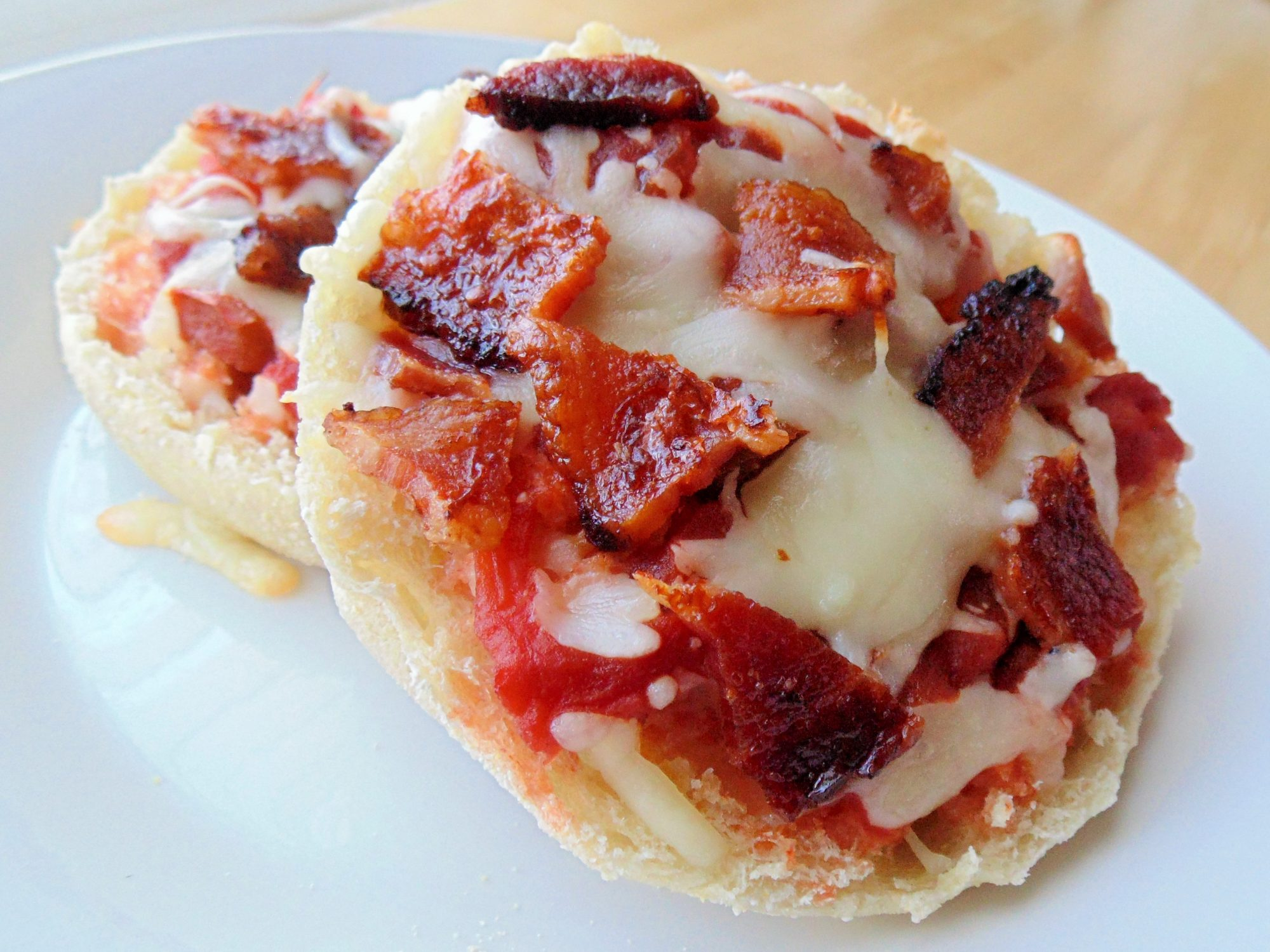 two english muffins with tomato sauce, cheese, and bacon