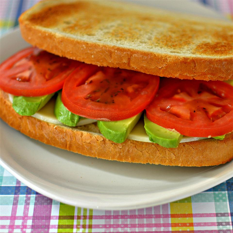 tomatoes, avocadoes, and provolone on sandwich