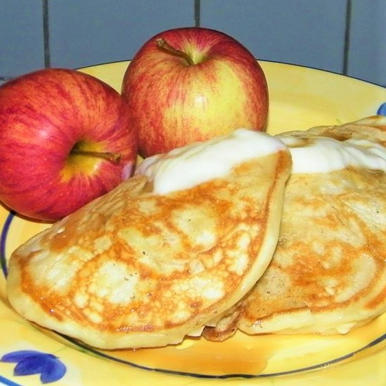 apple yogurt pancakes on a yellow plate with two apples in the background