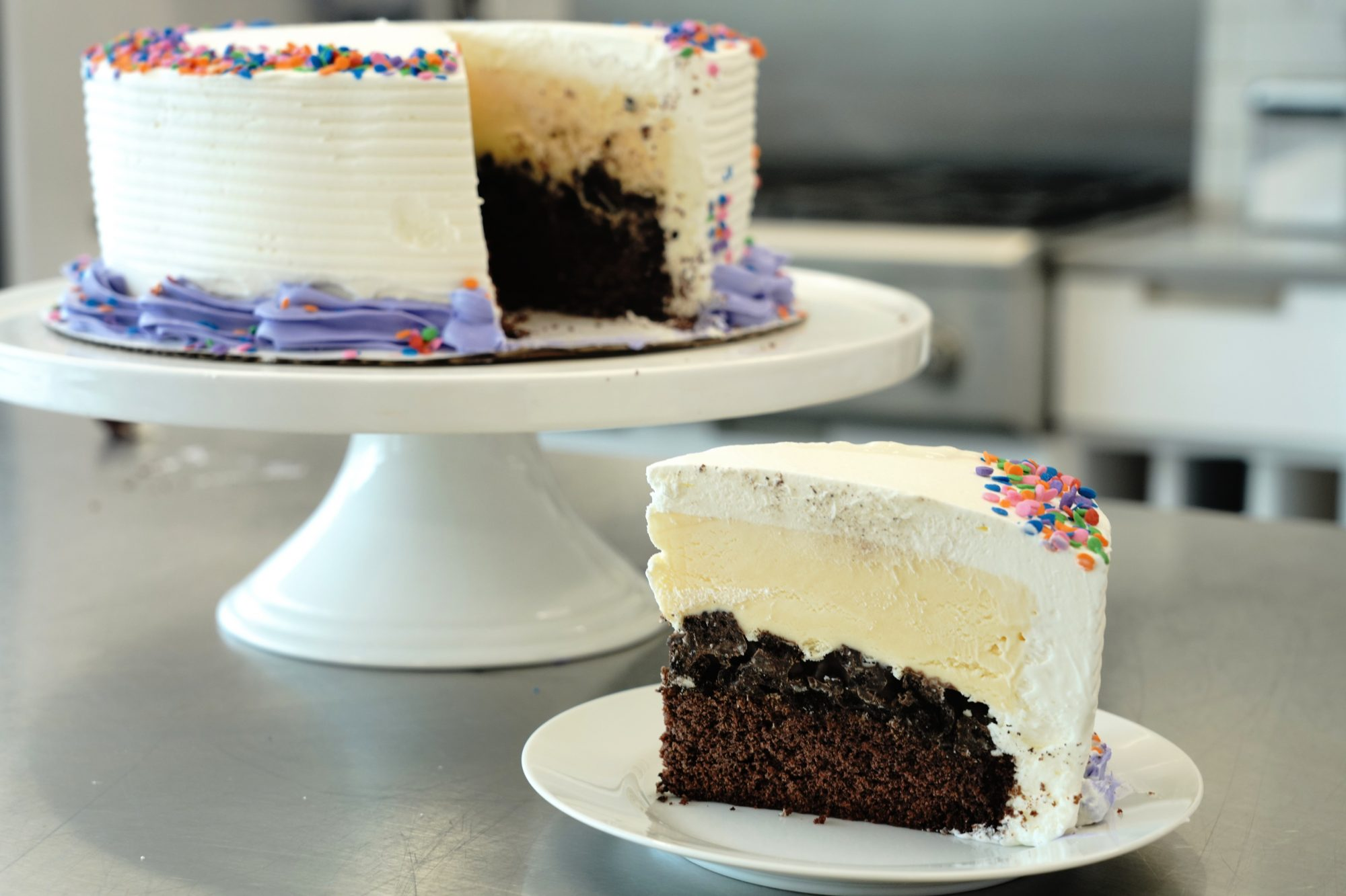 side view of a slice of homemade ice cream cake with a chocolate cake base, crunchy cookie filling, vanilla ice cream top layer, and whipped cream frosting with candy sprinkles