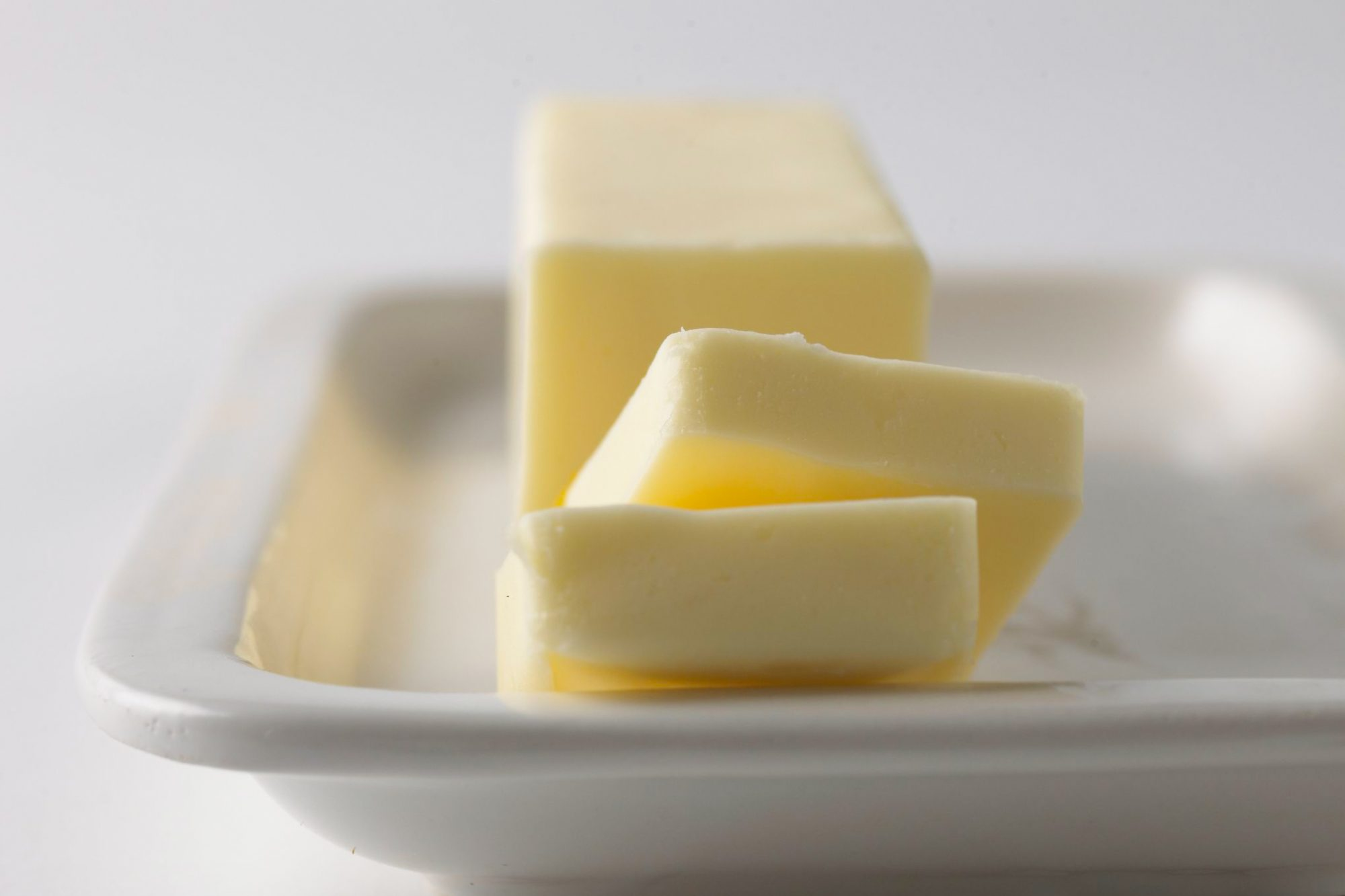 Stick of butter with a few slices cut on a white platter