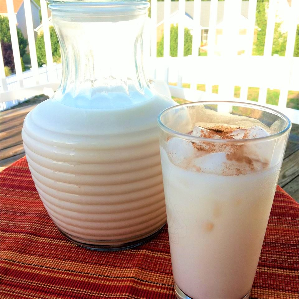 horchata in a tall glass with a pitcher in the background