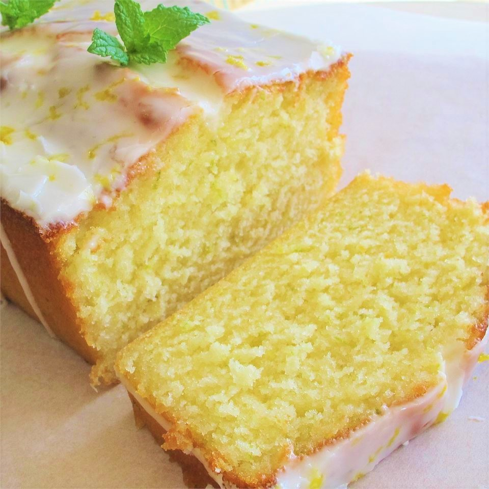 an iced lemon loaf cake sliced and garnished with mint