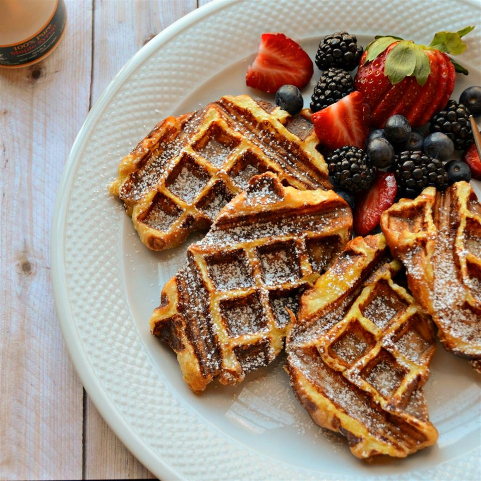 overhead shot of French toast waffles with powdered sugar and berries on a plate