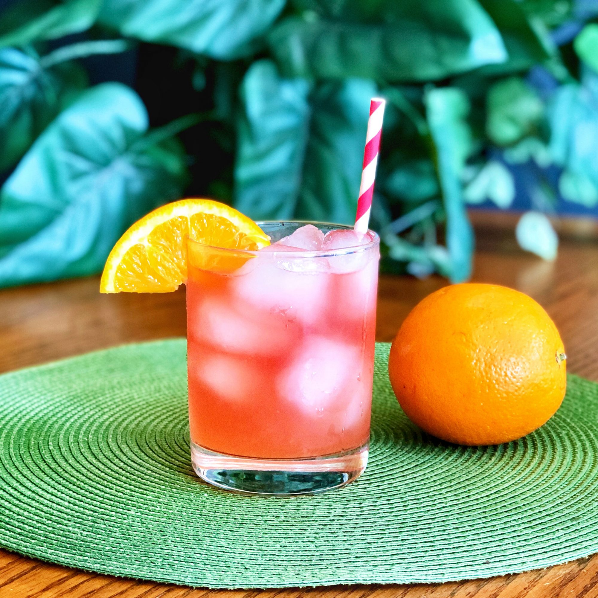 red cocktail in tumbler glass with straw and orange wedge
