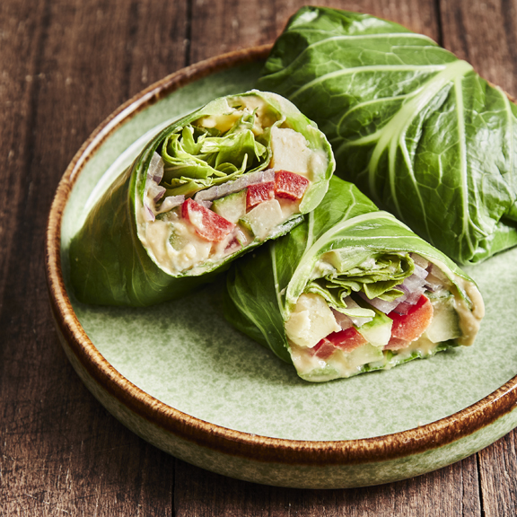 Two collard green wraps plated with one sliced in half to show the colorful veggies inside