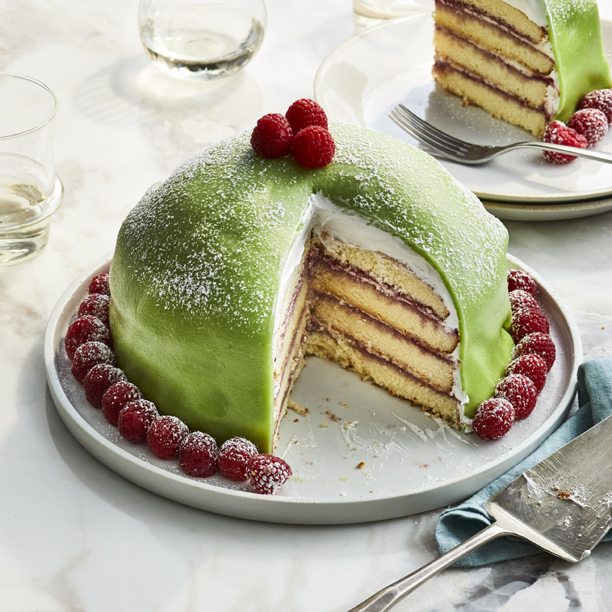 A classic dome shaped Swedish princess cake wrapped in pale green marzipan, dusted with powdered sugar, and decorated with raspberries. A slice out reveals all the beautiful layers