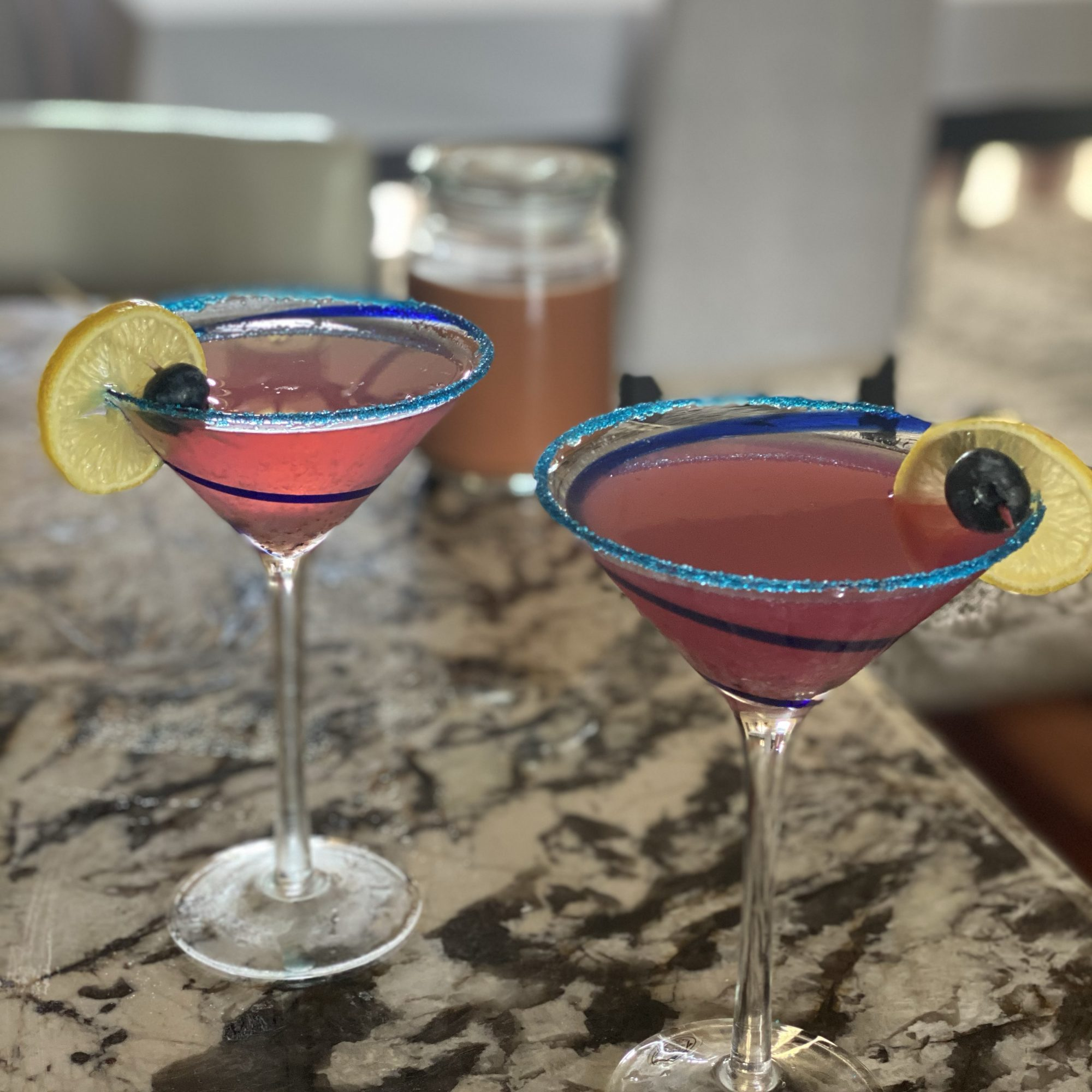 two purple cocktails in martini glasses with lemon wedges