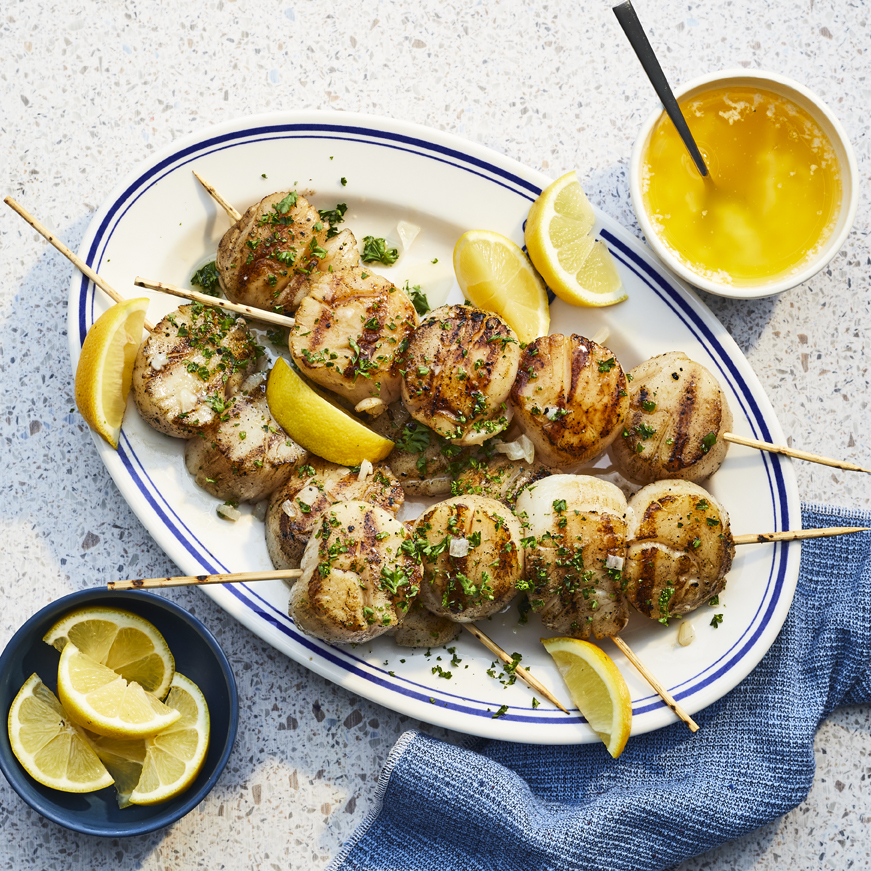 Oval platter with beautifully grilled, skewered, scallops. Warm citrus butter and extra lemon wedges on hand