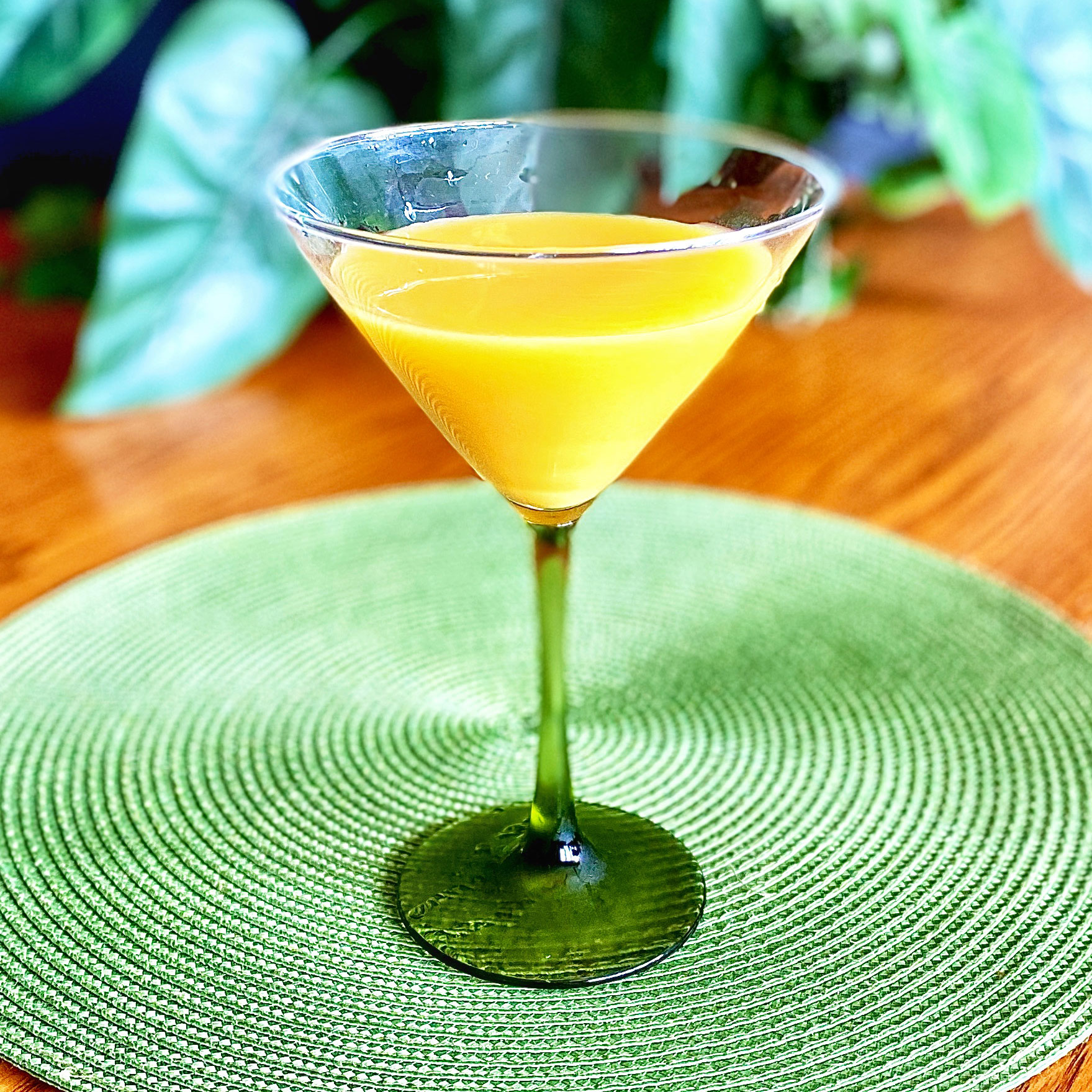 orange drink in martini glass on green placemat