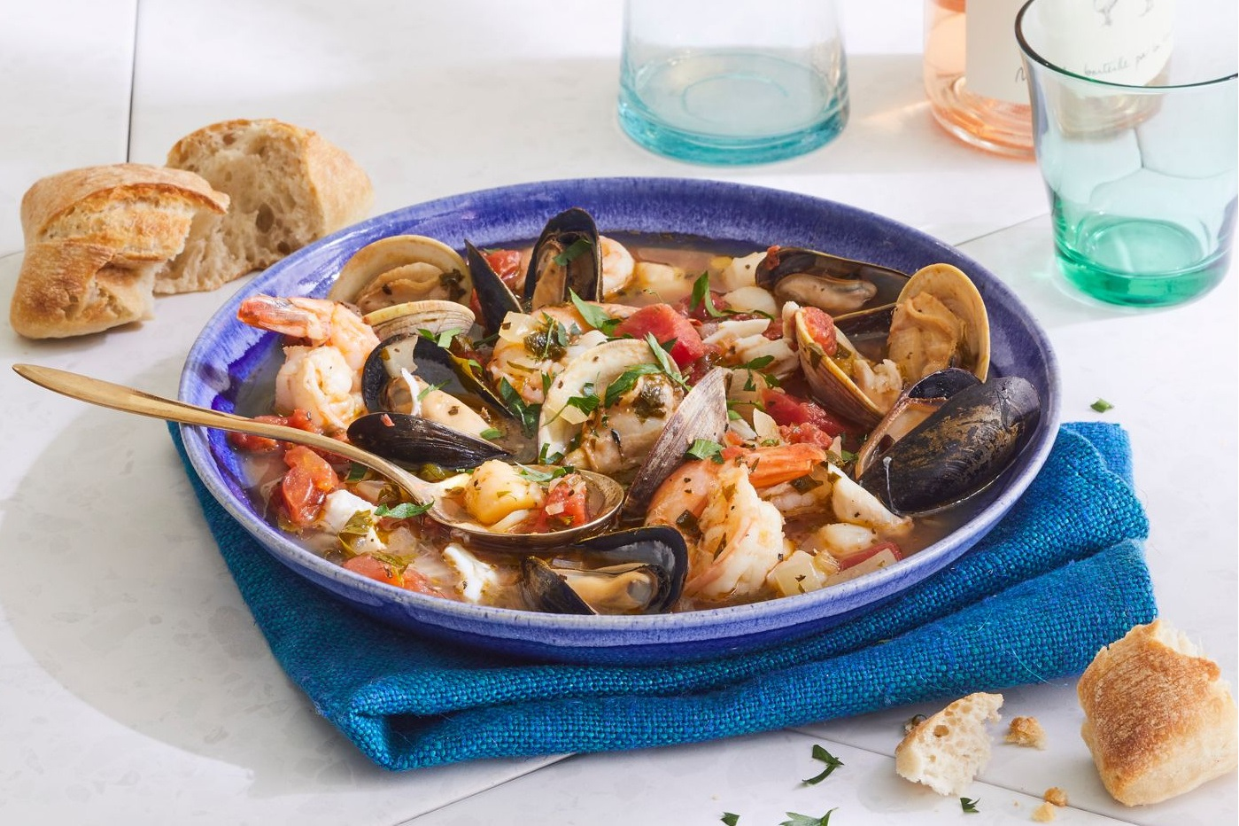 homemade cioppino in a bowl served with bread on the side