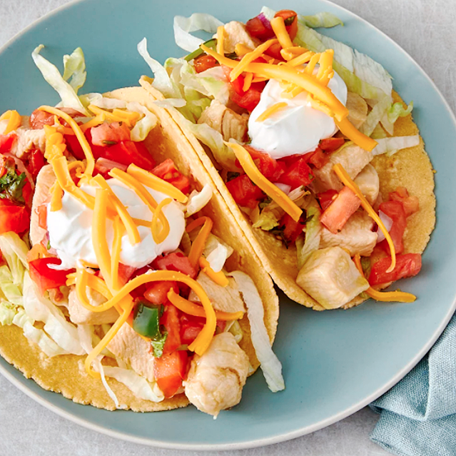 Two chicken tacos on corn tortillas, topped with onions, tomatoes, sour cream and shredded cheddar