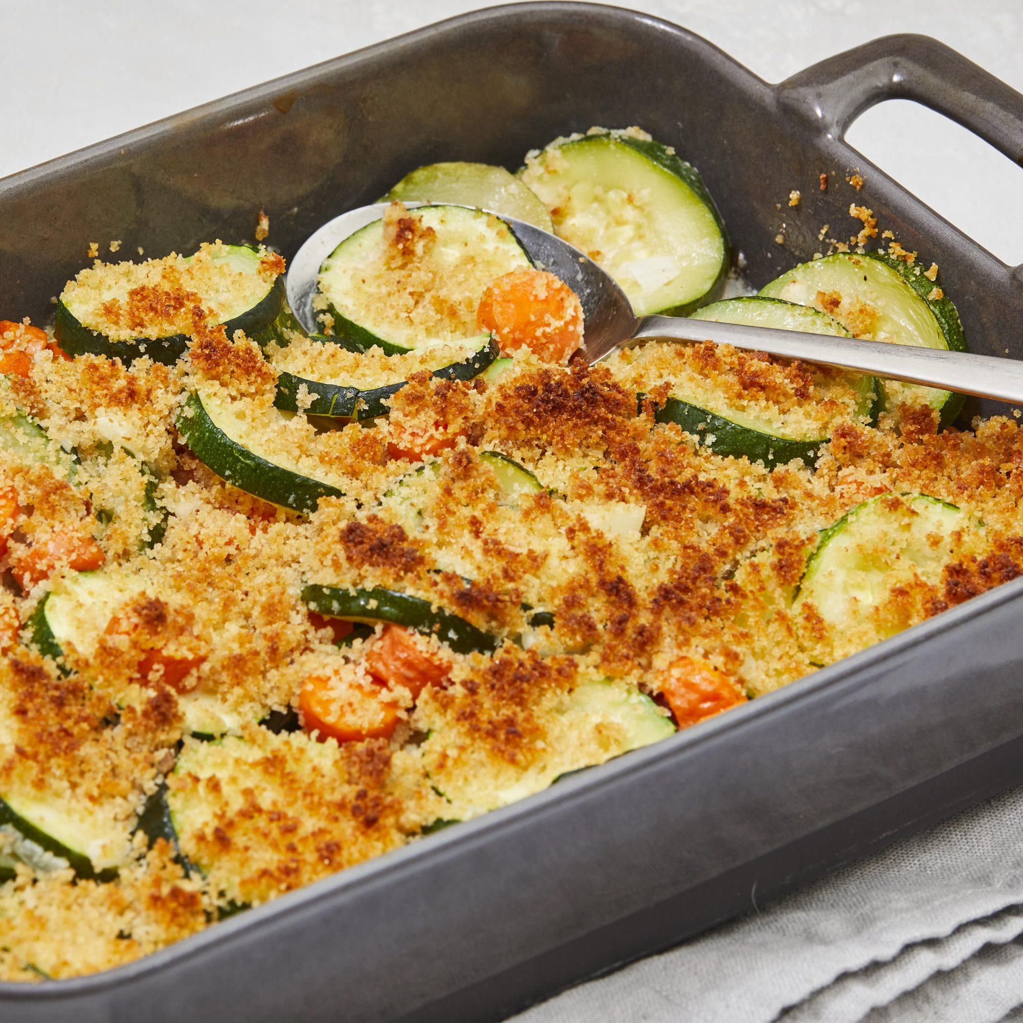 zucchini gratin in casserole dish with serving spoon