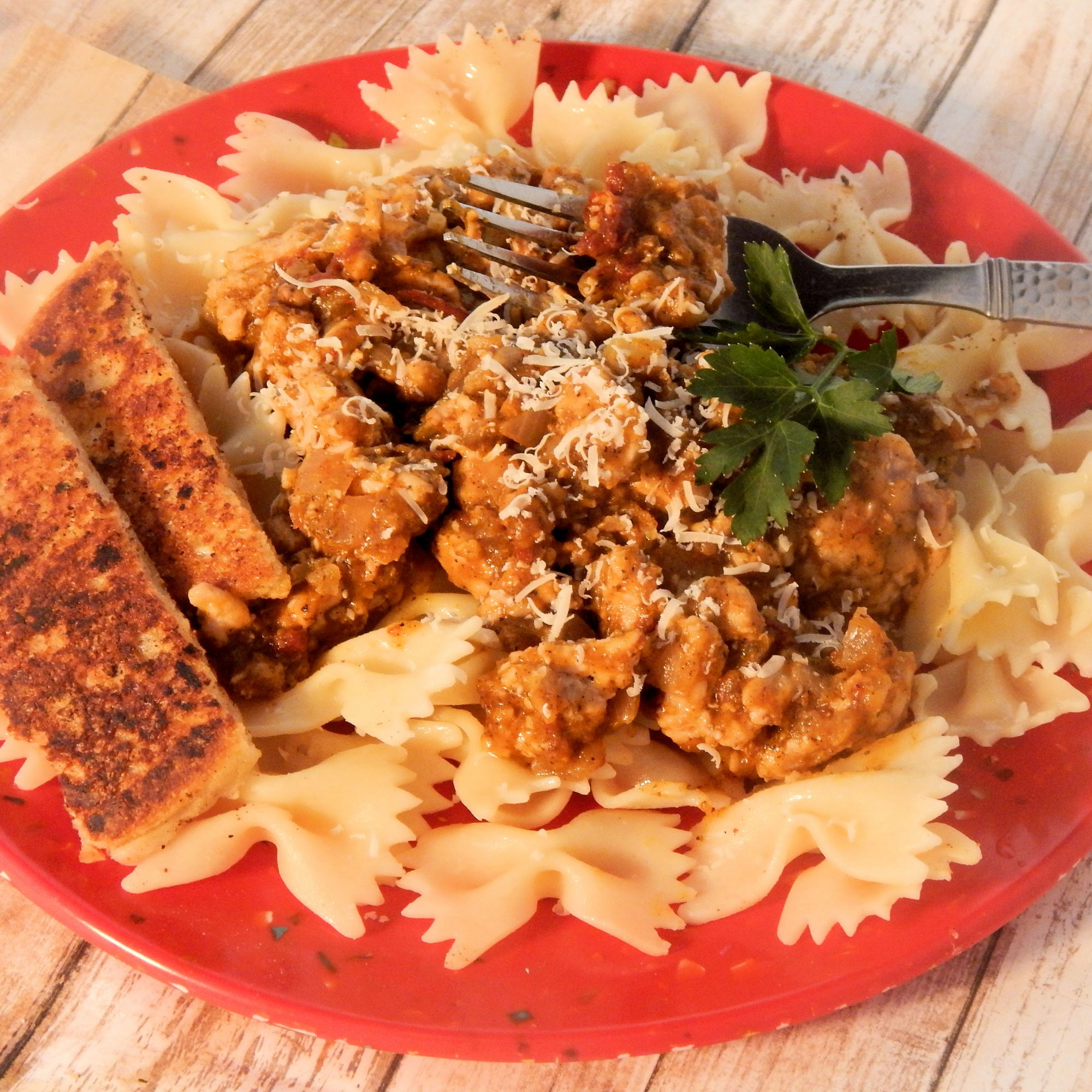 Sweet and Spicy Pumpkin Turkey Pasta on a red plate