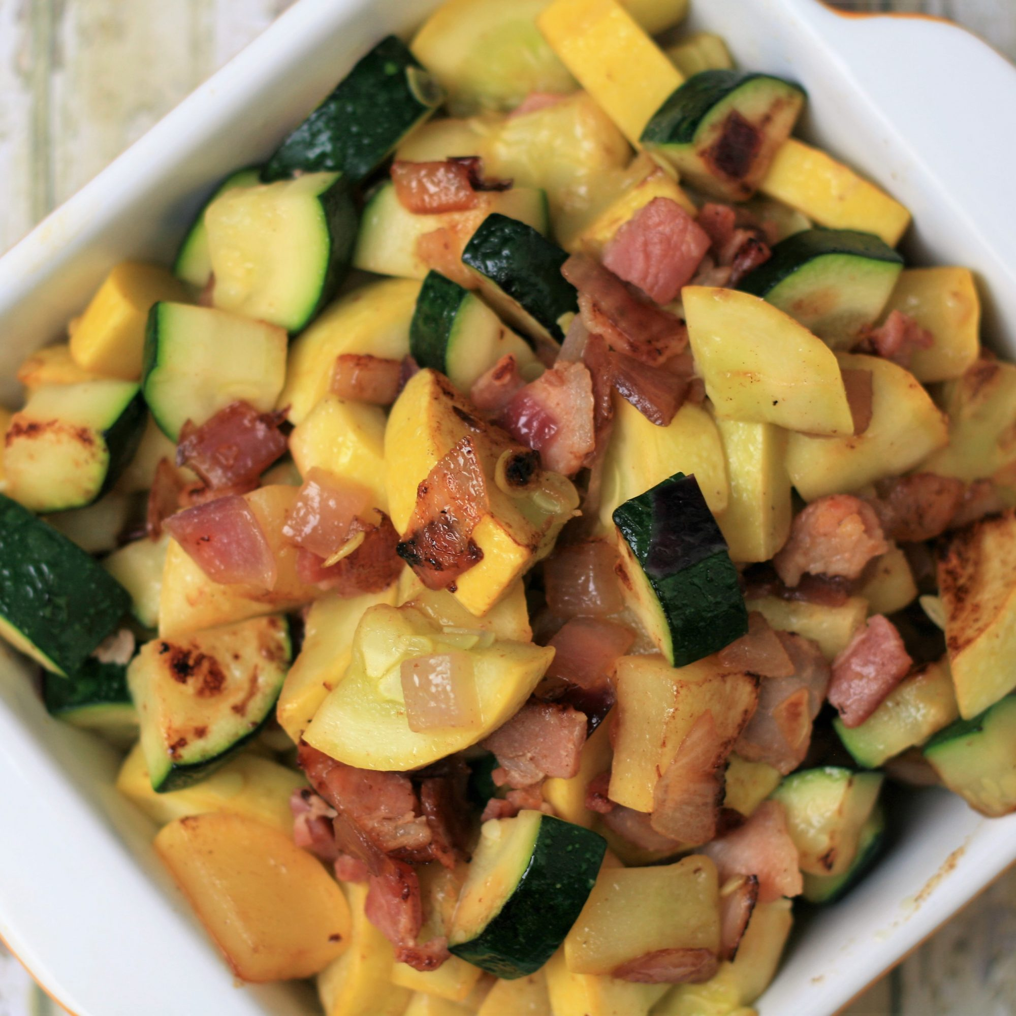 Summer Squash Saute with Bacon in a white bowl