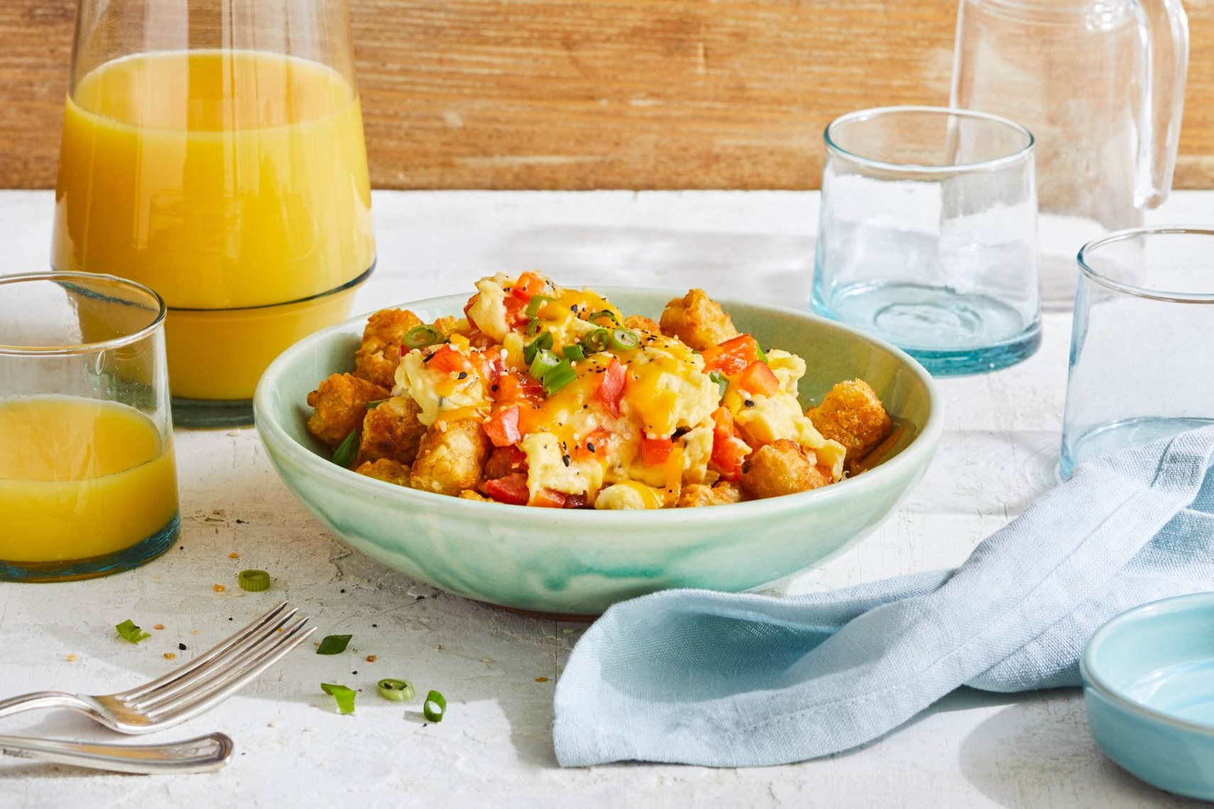 breakfast bowl with tater tots, scrambled eggs, bell peppers, green onions, cheese, and salsa