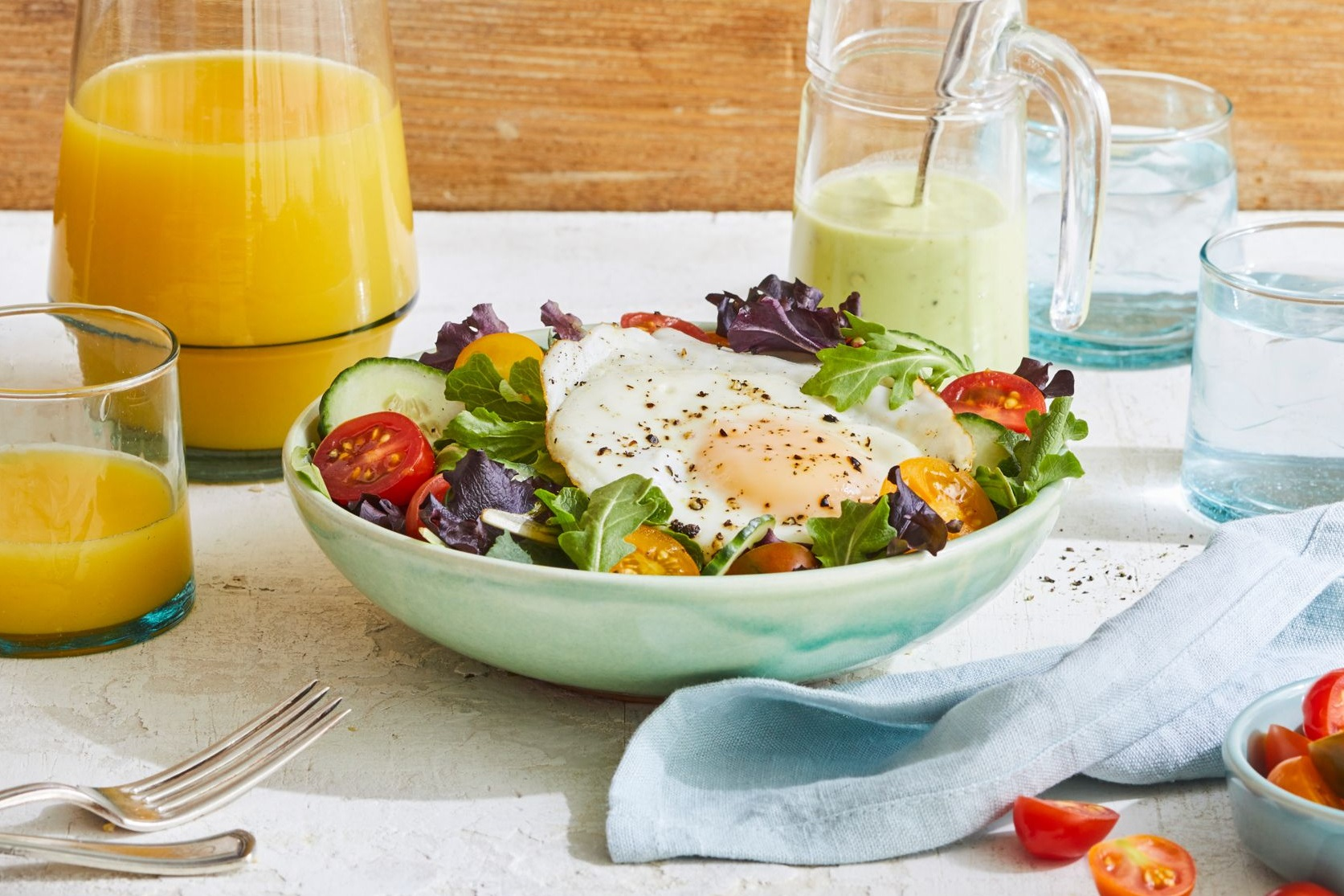 breakfast bowl with bacon and eggs over salad greens and tomatoes with avocado yogurt dressing