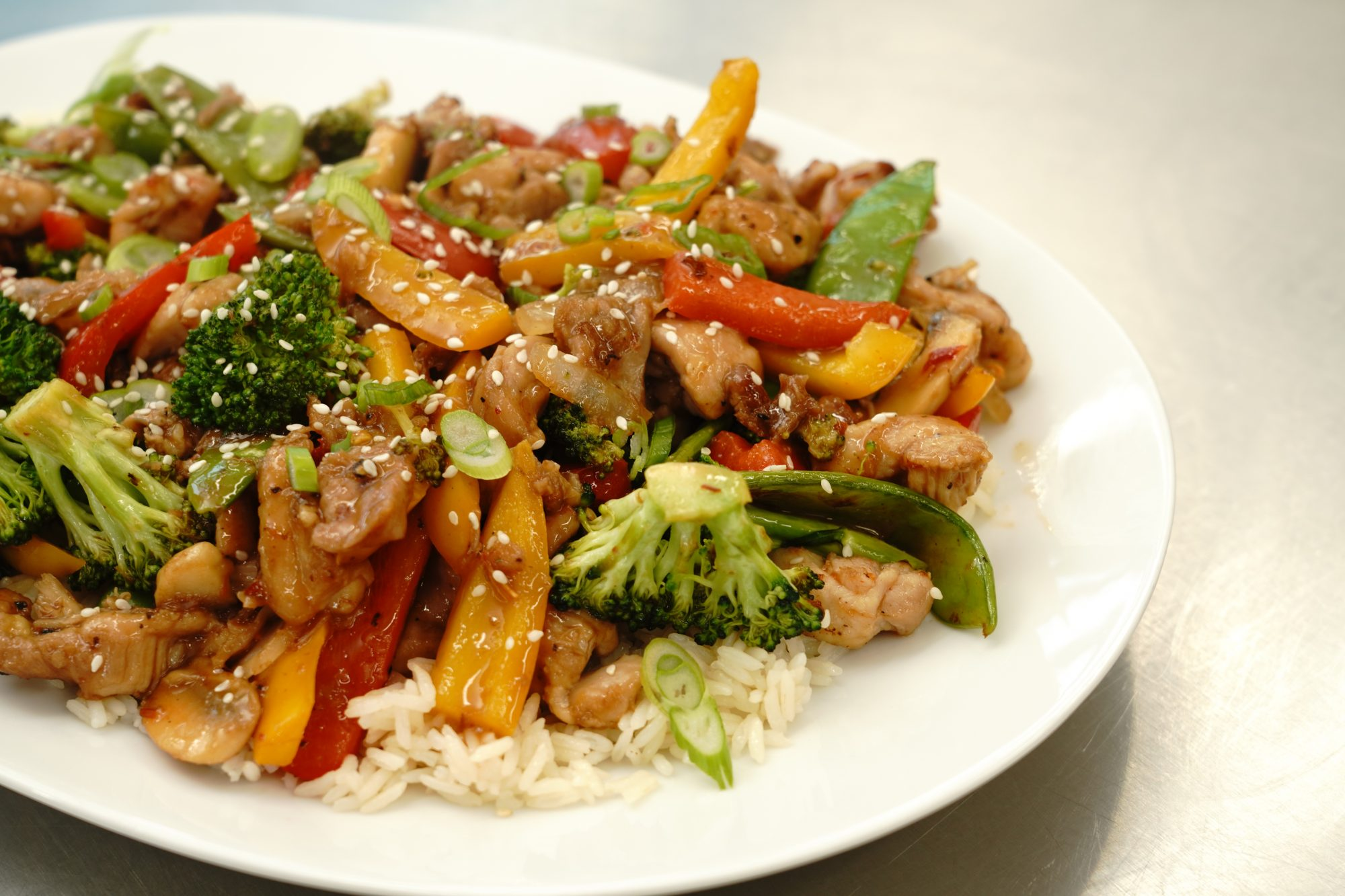chicken stir fry with vegetables served over rice