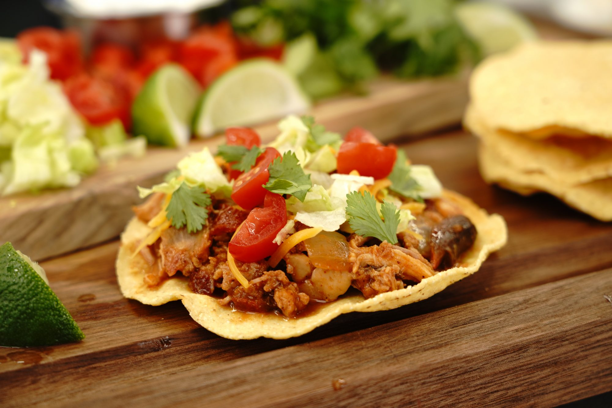 slow cooker chicken tinga on tostada shell topped with lettuce, tomatoes, and cilantro