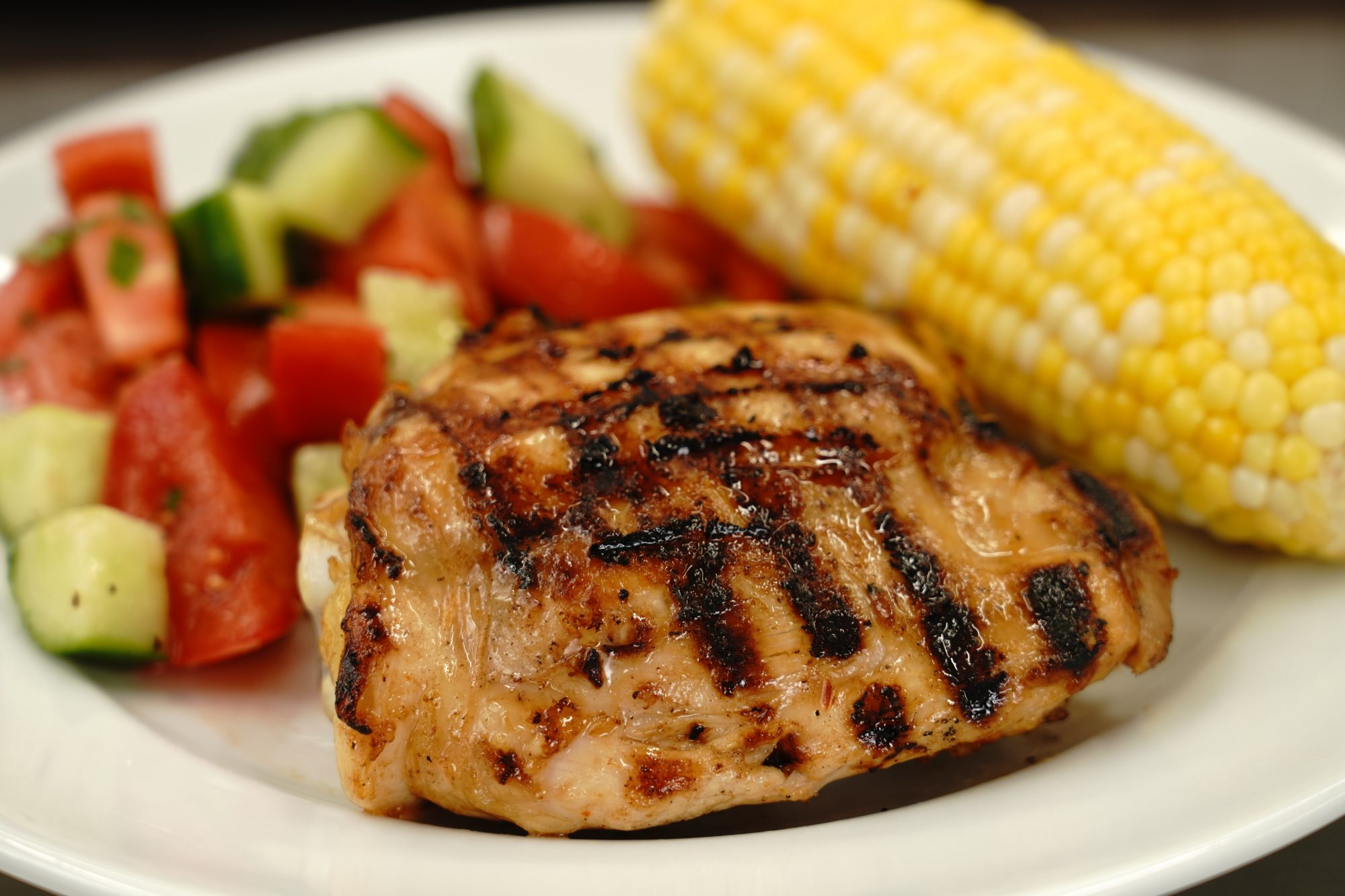 grilled rusty chicken thighs recipe served with corn and tomato cucumber salad