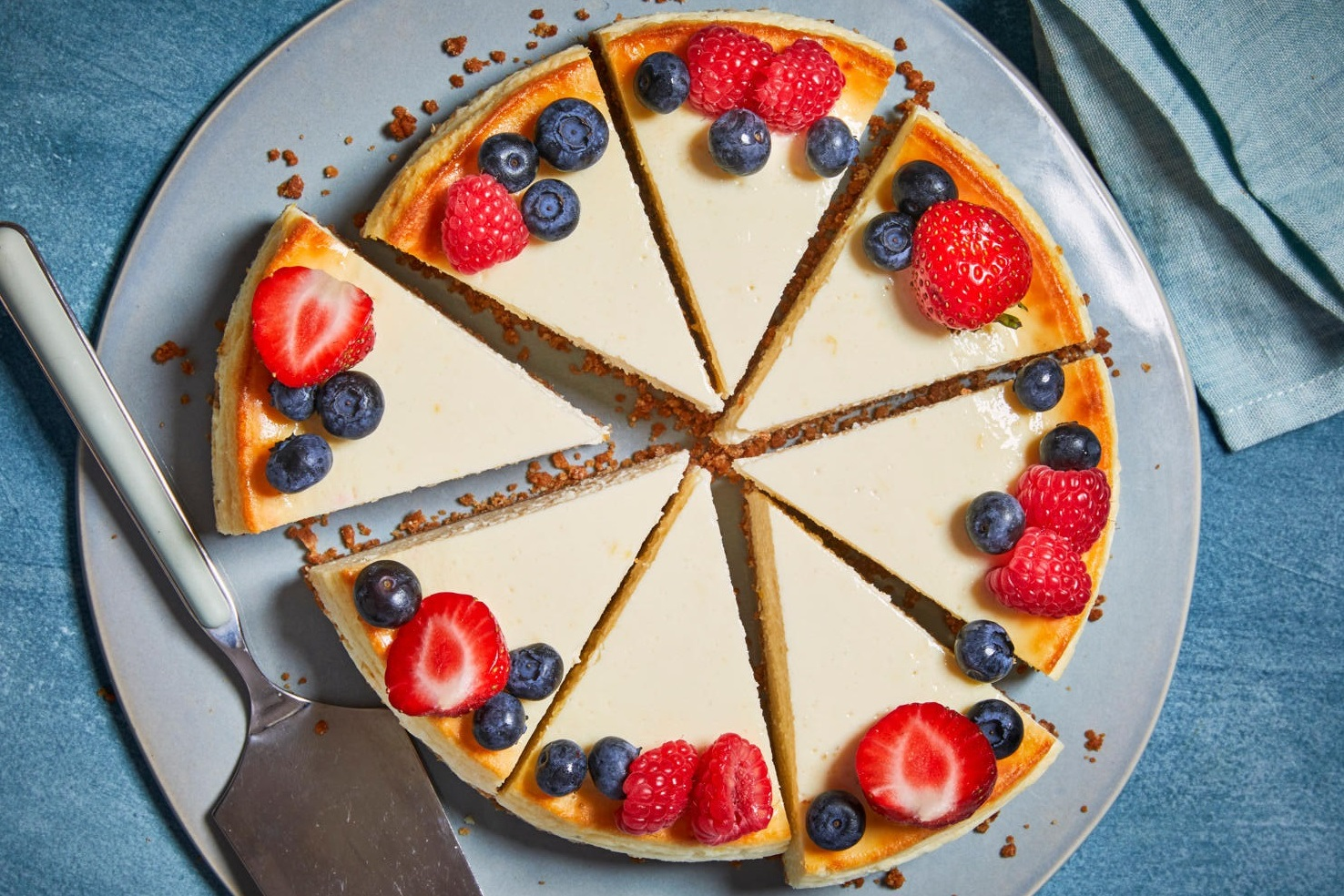 overhead shot of cheesecake topped with fresh strawberries, blueberries, and raspberries
