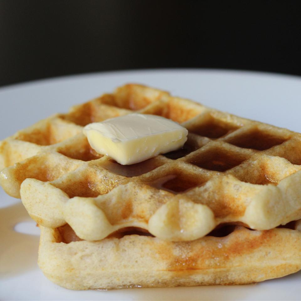two waffles on a white plate topped with butter