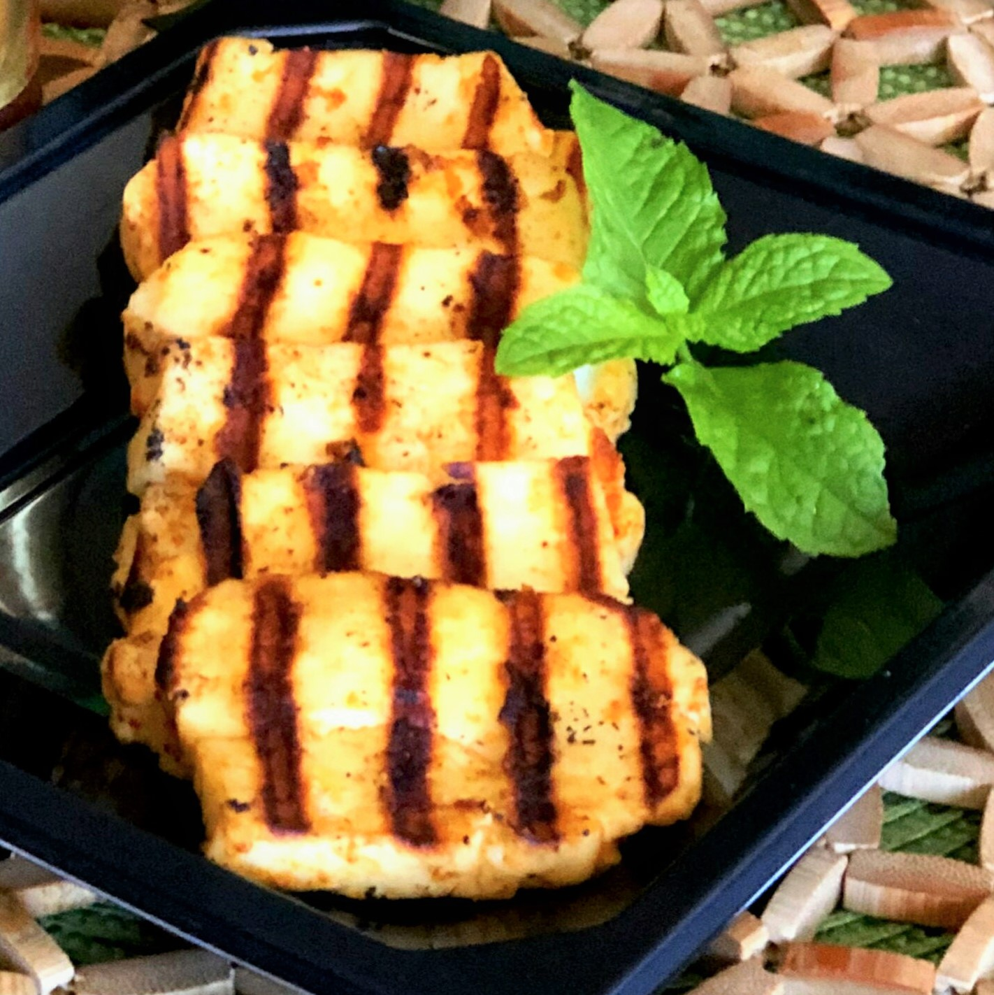 grilled spicy halloumi on a black plate