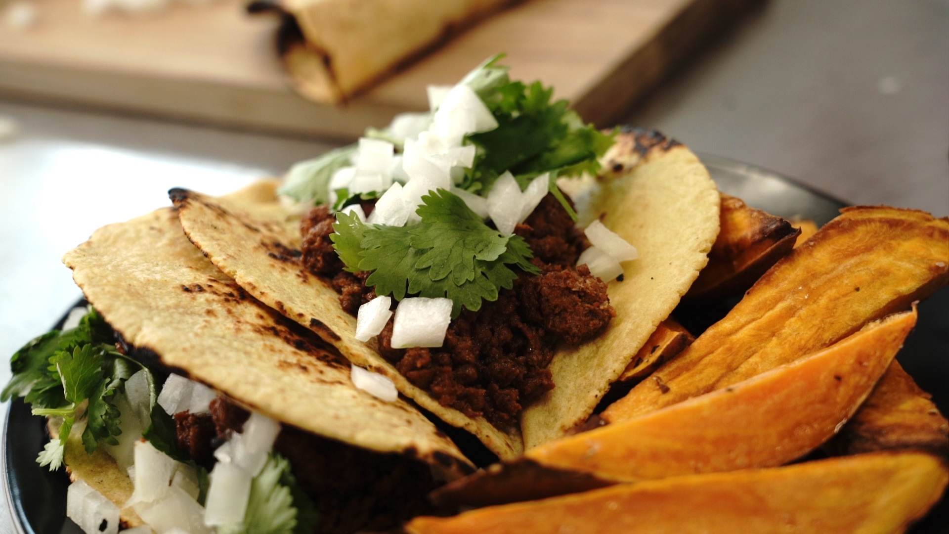easy chorizo street tacos topped with cilantro and chopped onions with roasted sweet potato wedges