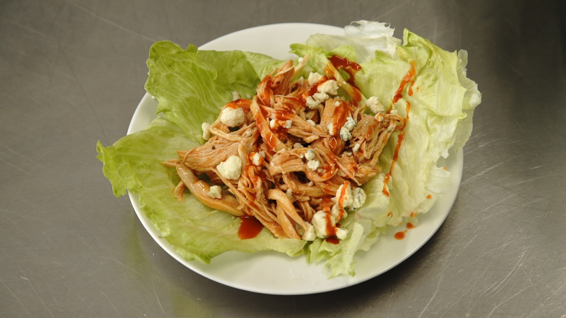 shredded buffalo chicken topped with hot sauce and crumbled blue cheese in a lettuce wrap