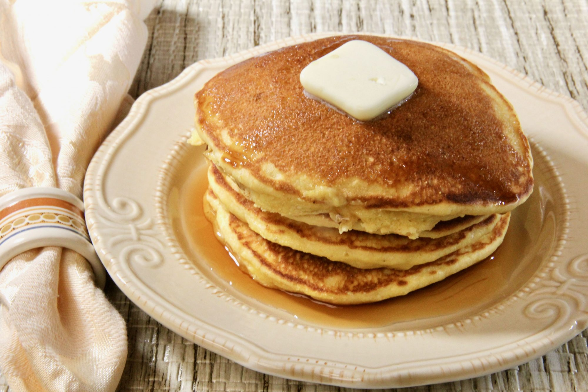 stack of pancakes on ceramic plate with butter