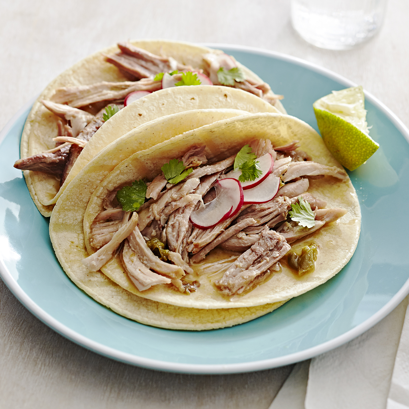 Andy's Spicy Green Chile Pork recipe on a blue plate