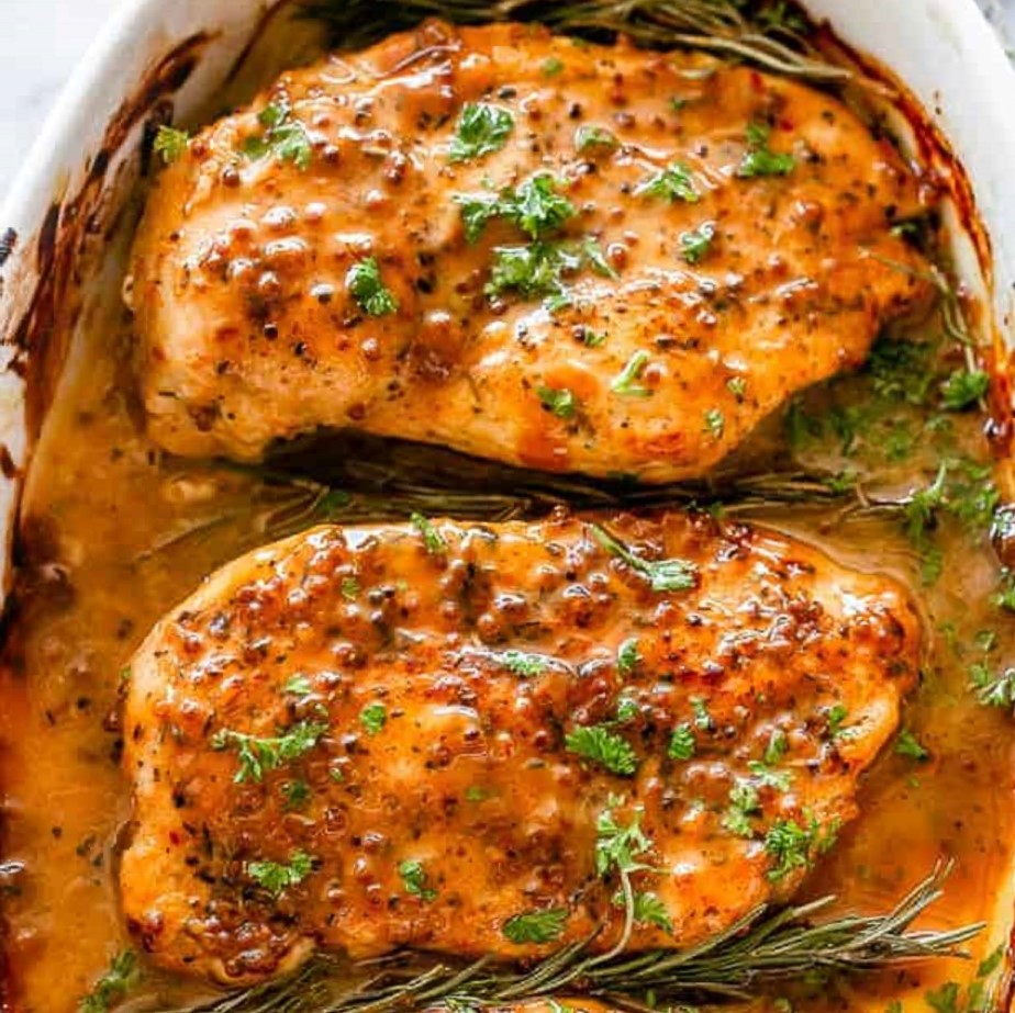 baked boneless chicken thighs with honey and mustard in a white baking dish