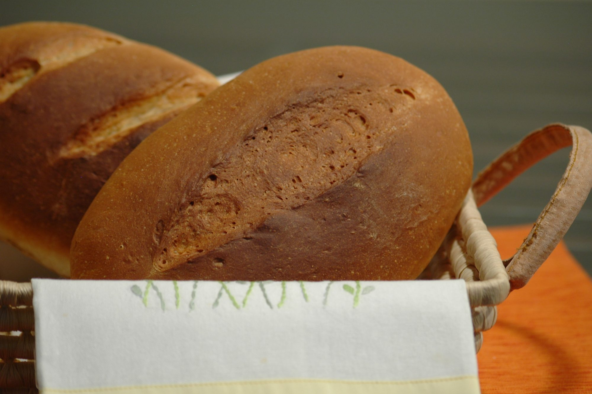 two loaves of bread arranged in a basket with a cloth napkin